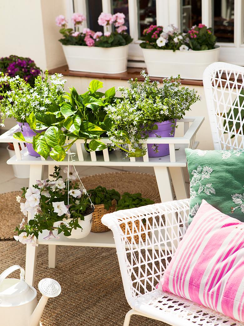 mueble para plantas en blanco con dos niveles silla de exterior con cojines y alfizar