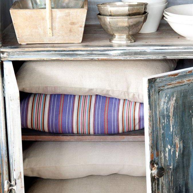 detalle armario aparador con cojines y vajilla