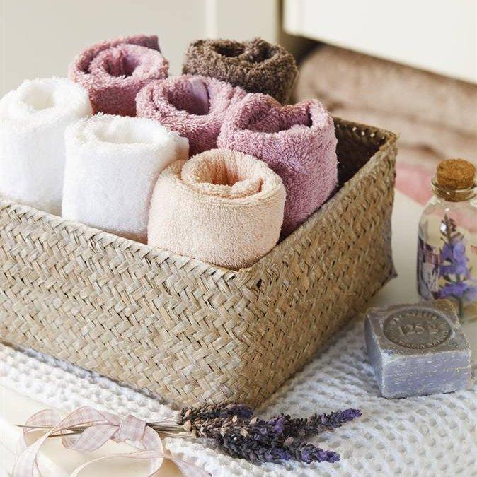 Detalle toallas de baño de colores en cesta de fibras en el baño