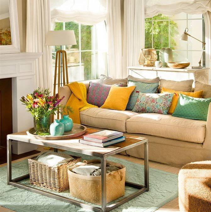 Salón con cojines de colores, lámpara de pie en madera y tela, mesa de centro madera y metal y cestas de fibra natural