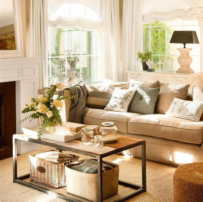 Salón en tonos neutros con sofá beige, cojines grises y marrones, mesa de centro y flores