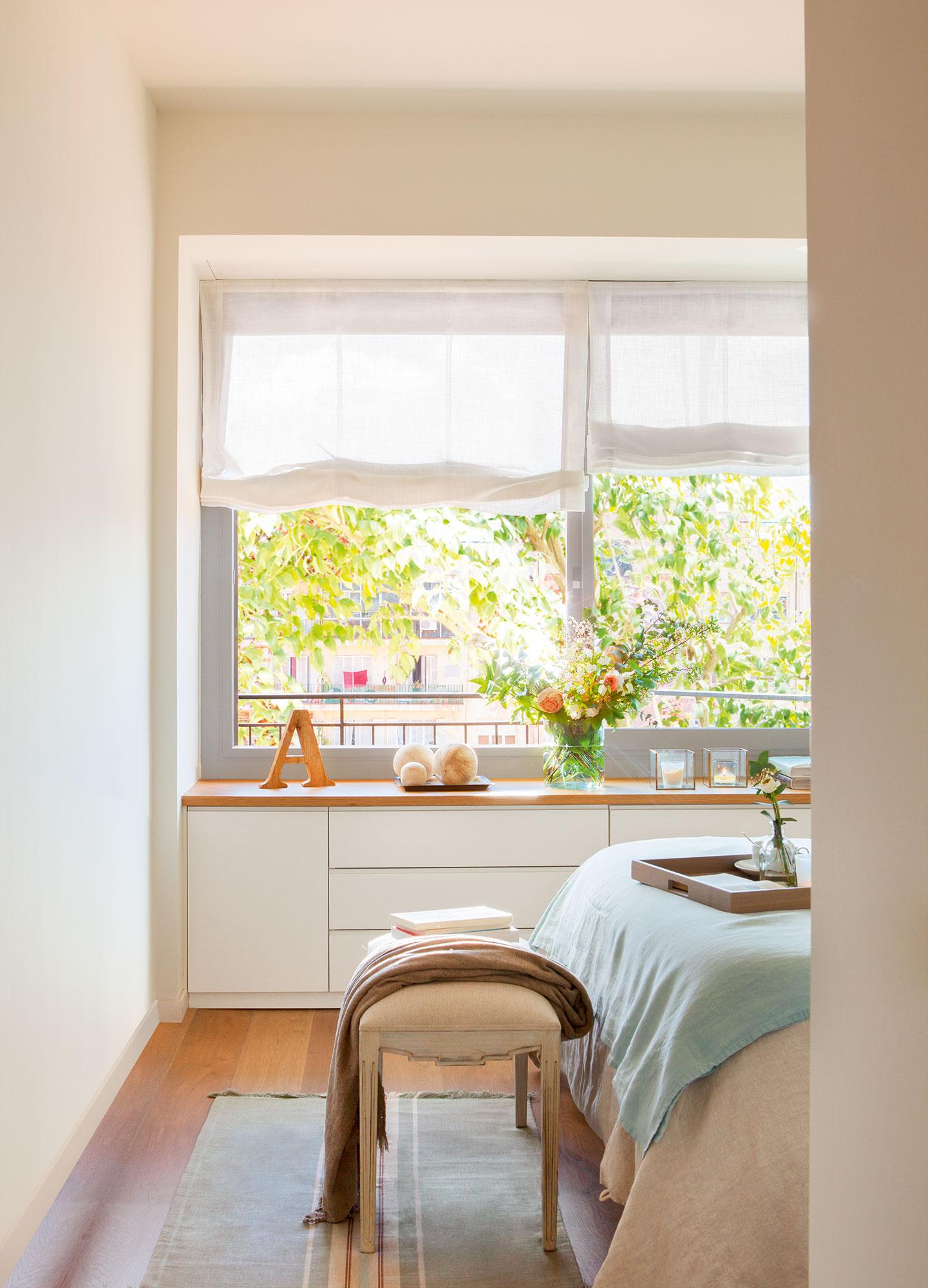 los pies de la cama una banqueta y bajo la ventana un pequeño mueble