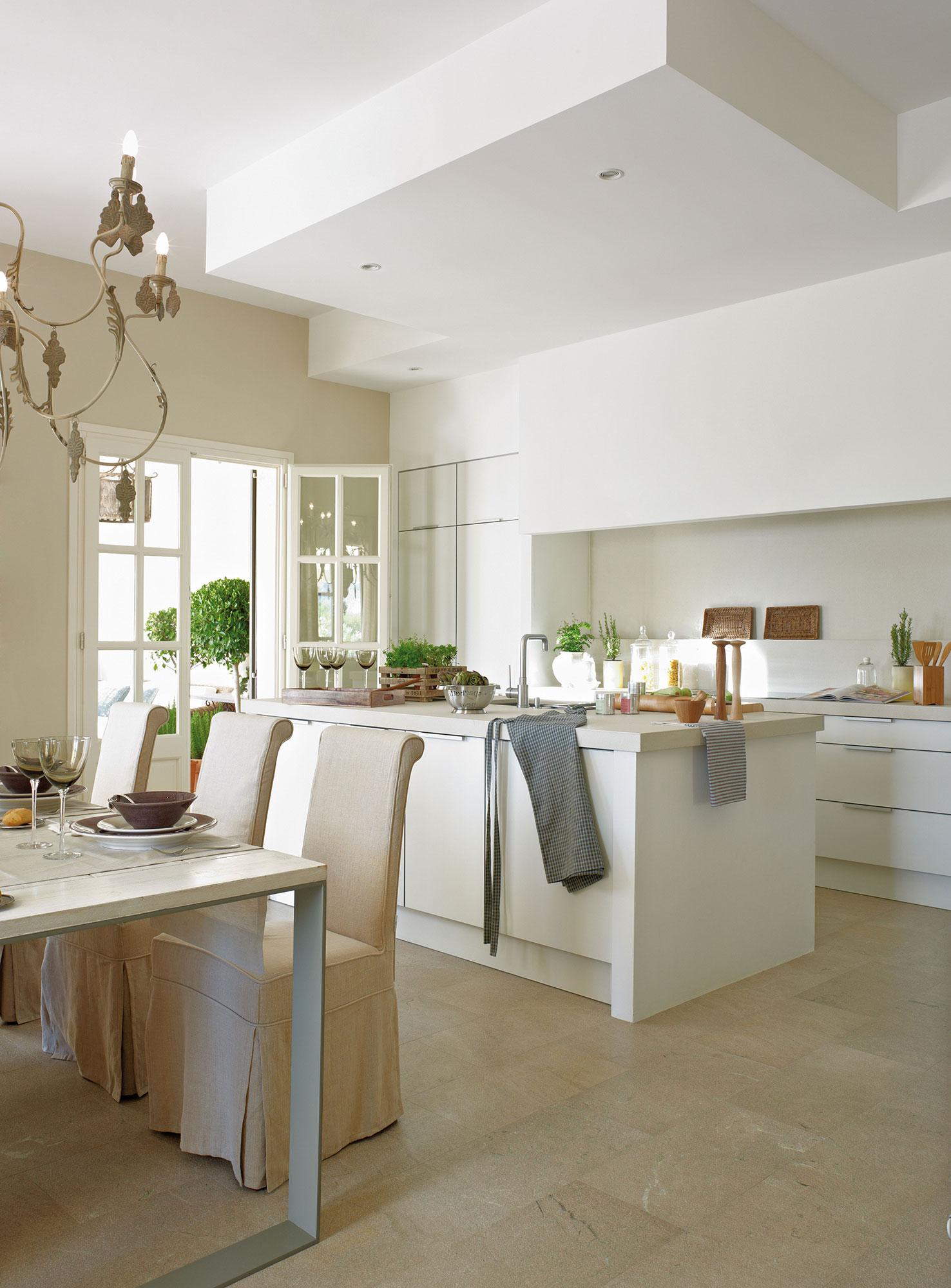 cocina blanca con isla central y office con sillas con fundas