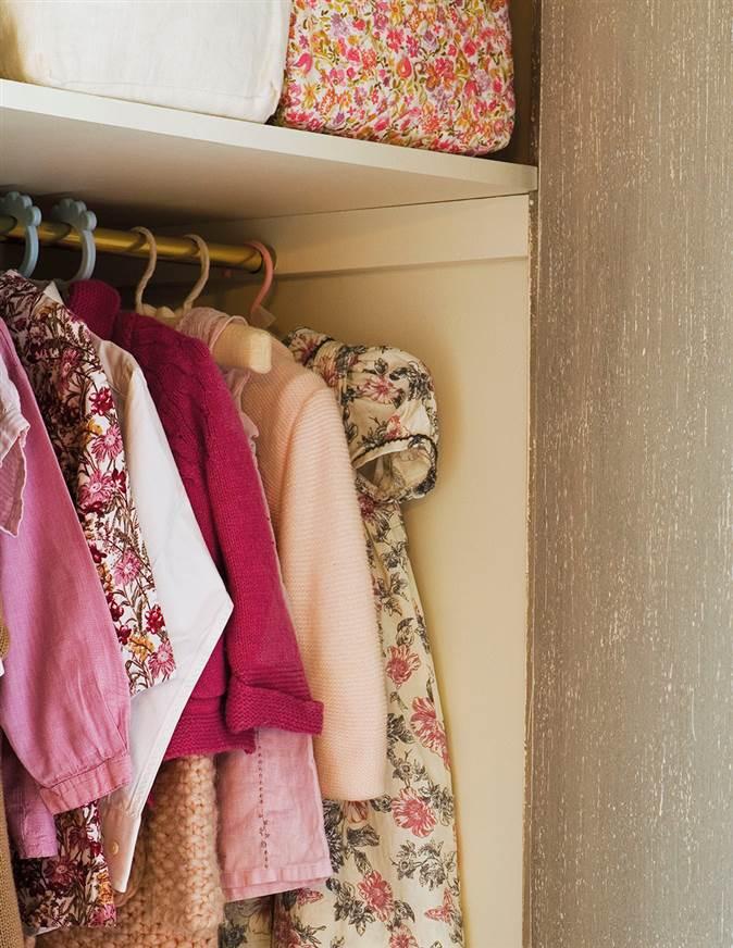 ropa de nia colgada en la barra del armario