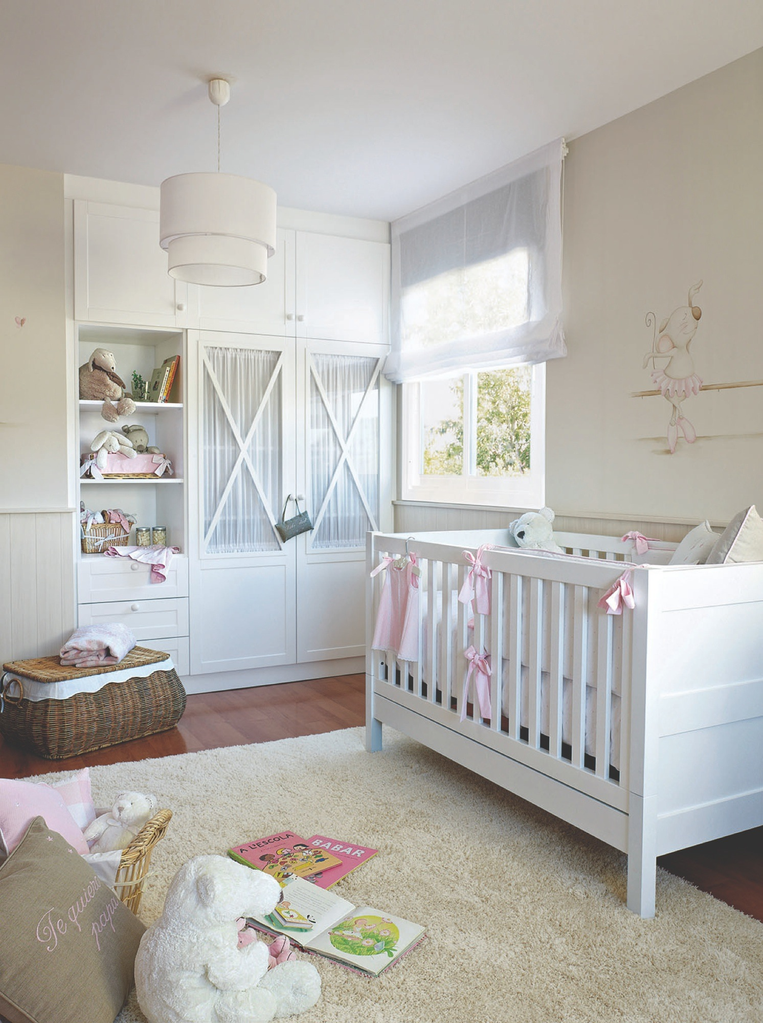 con espacio para sus primeros juegos dormitorio infantil en blanco con cuna y un armario