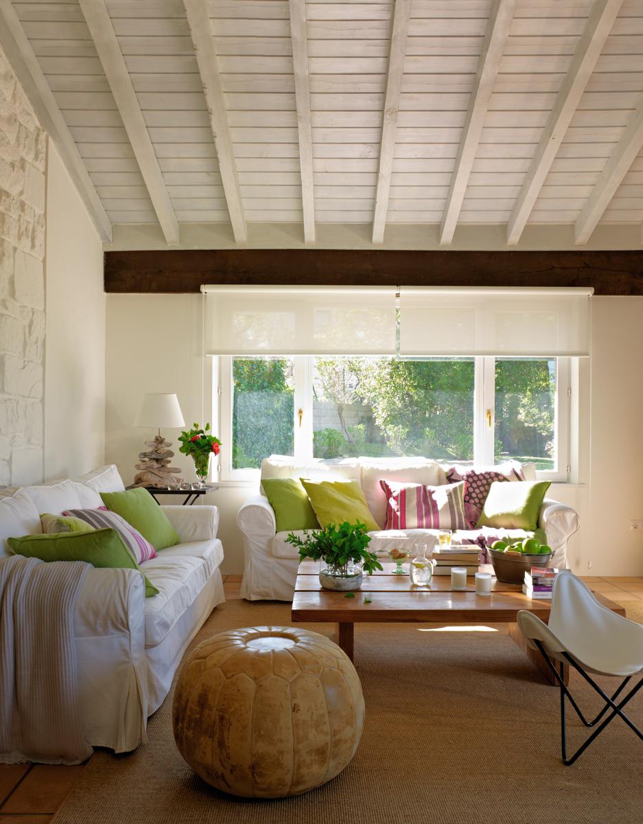 13-Salón-con-techo-abuhardillado,-sofá-blanco-con-cojines-verdes,-alfombra-de-fibra-natural-y-puf 301614