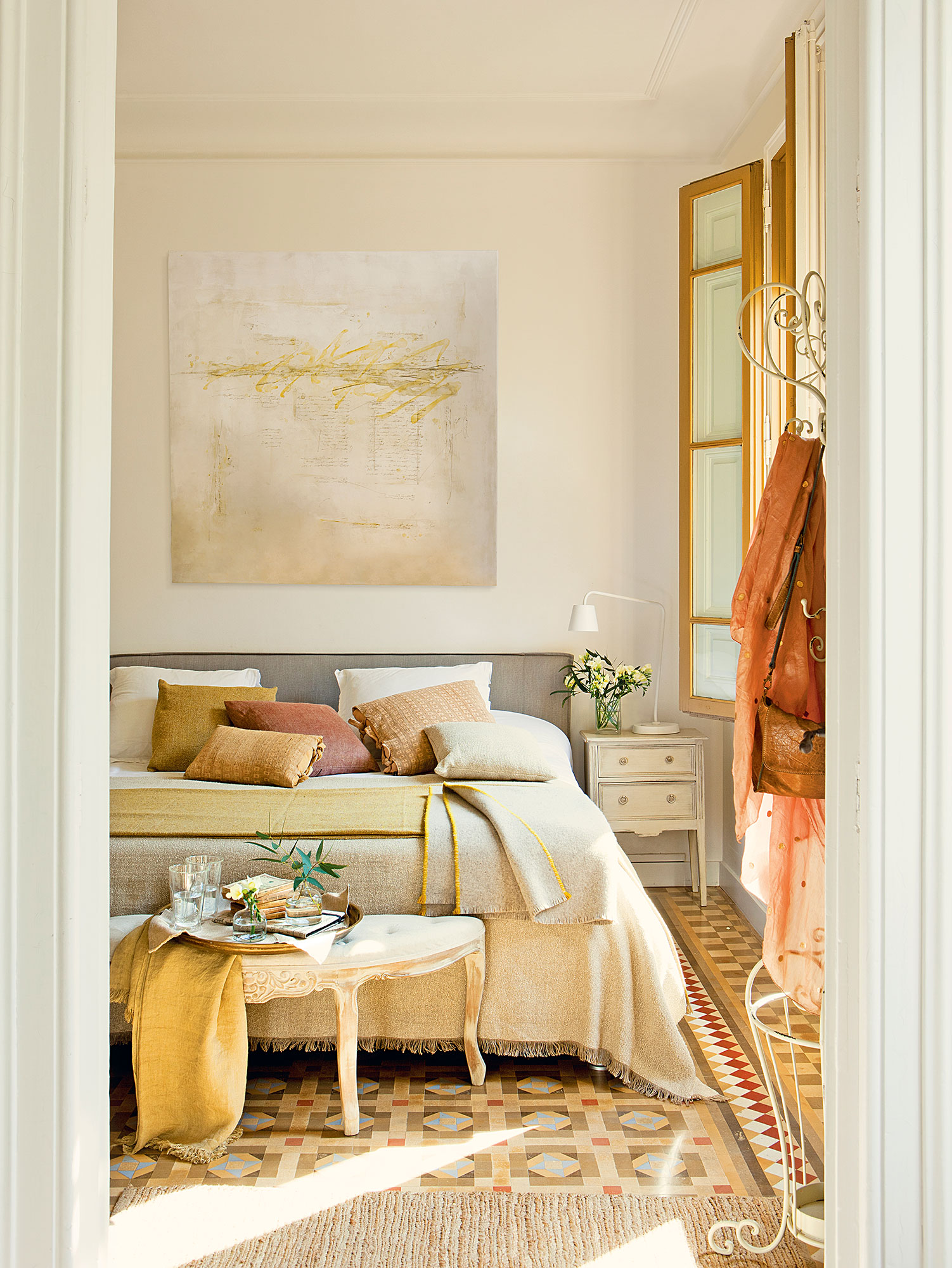 Dormitorio principal con ropa de cama en tonos ocres