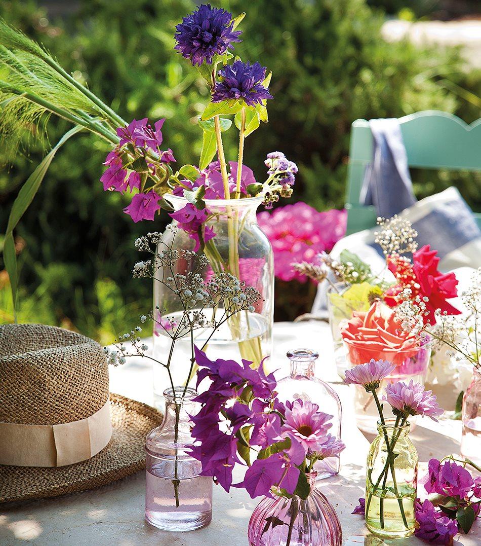 diferentes jarrones con flores sobre mesa de exterior
