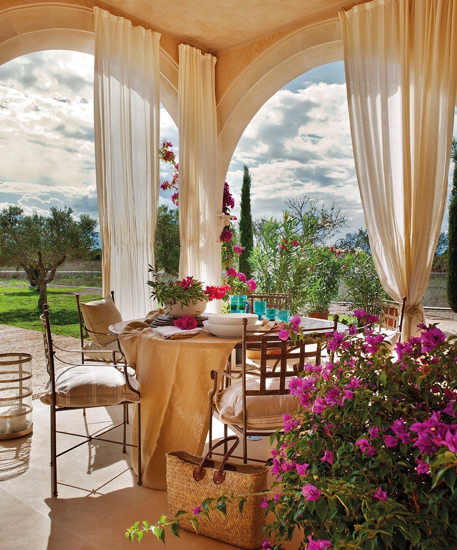 Comedor exterior bajo los arcos con buganvillas