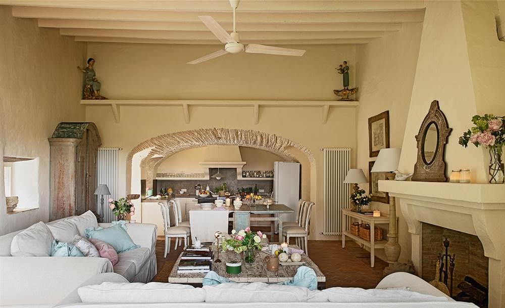 Salón con chimenea y techo de cañizo comunicado con la cocina