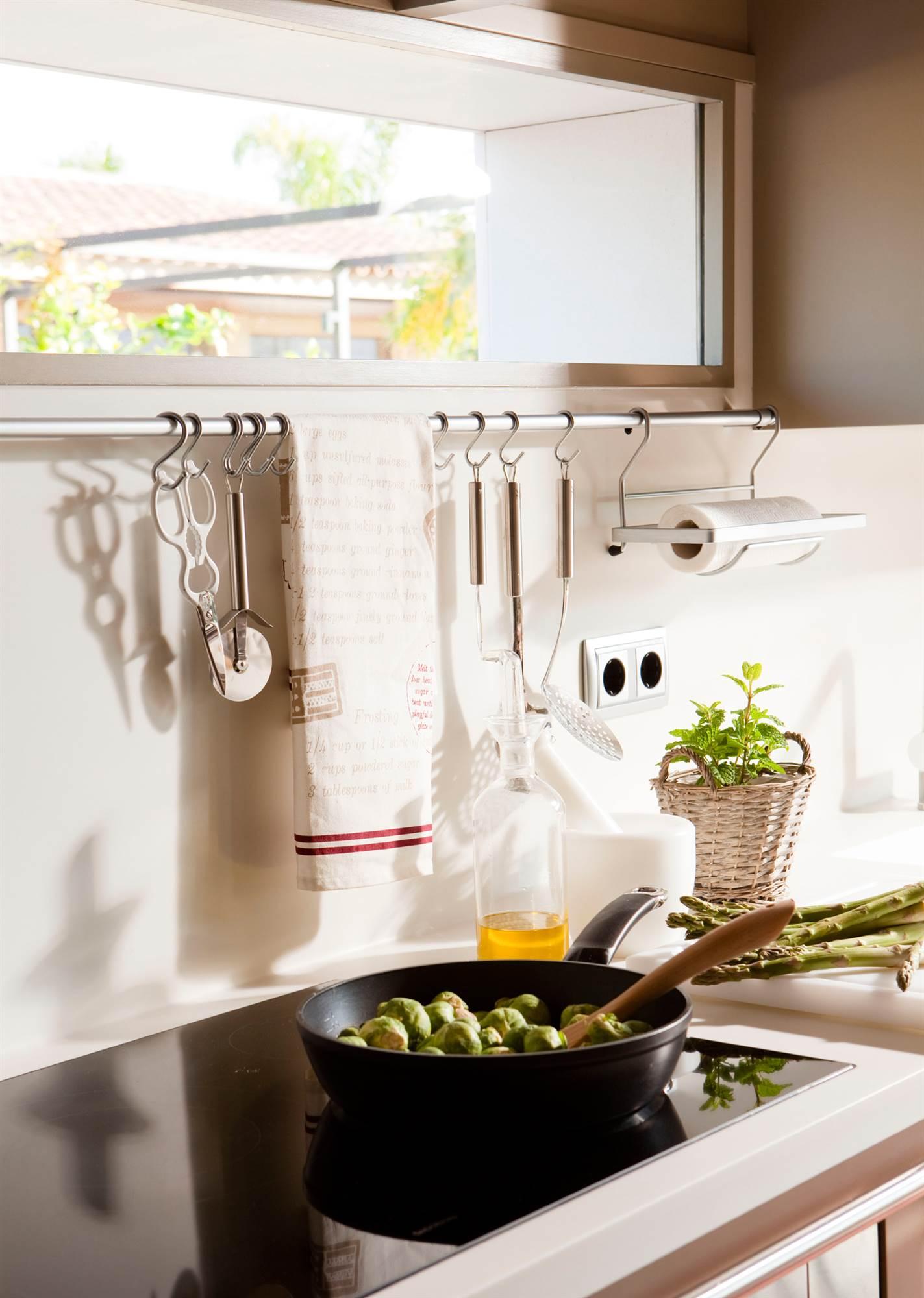14 00340855. Detalle de la encimera blanca de una cocina con vitrocerámica y una barra para colgar utensilios_14 00340855