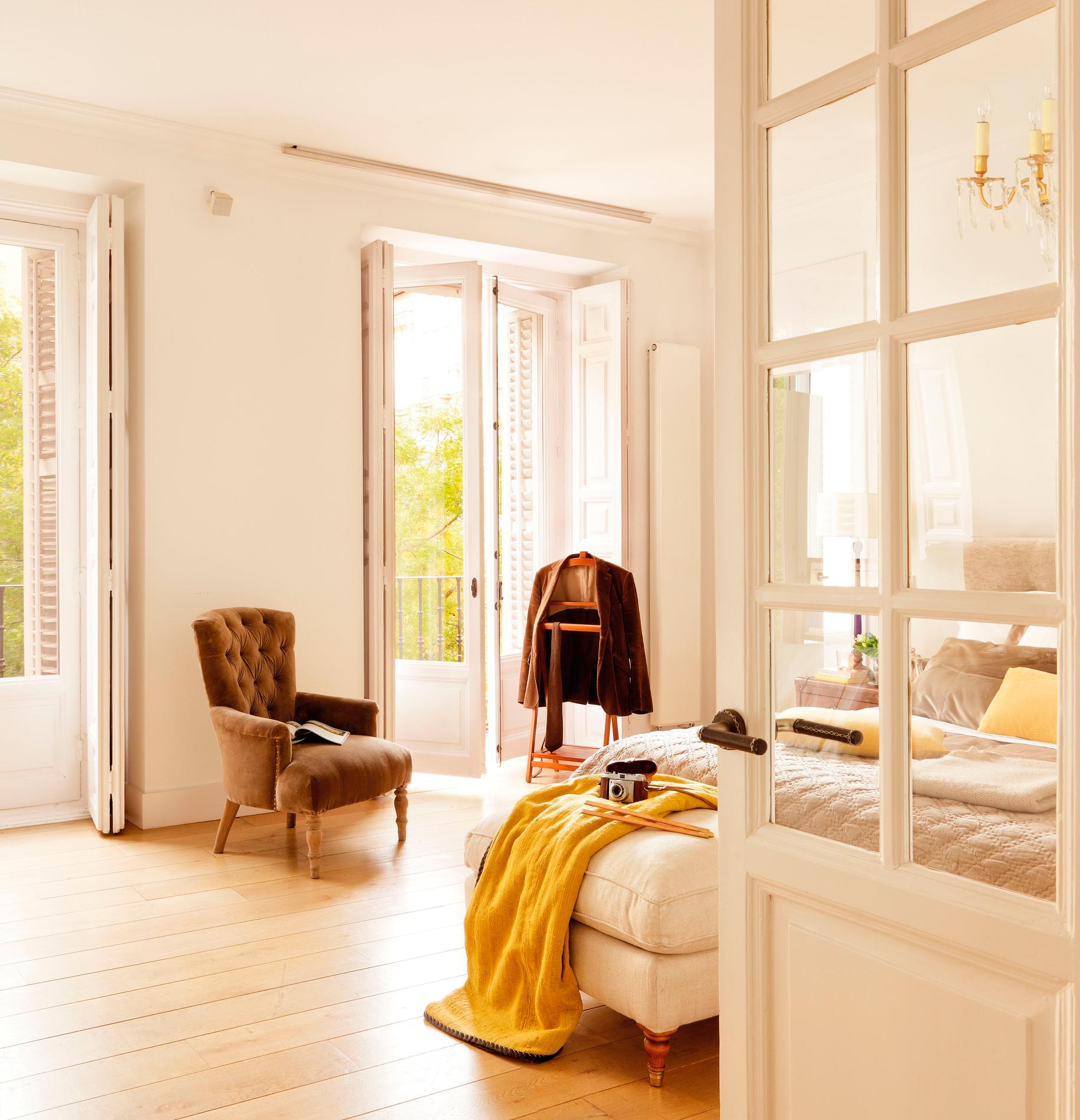 9 00336295. Amplio dormitorio blanco con ventanas al exterior y una butaca con capitoné_9 00336295