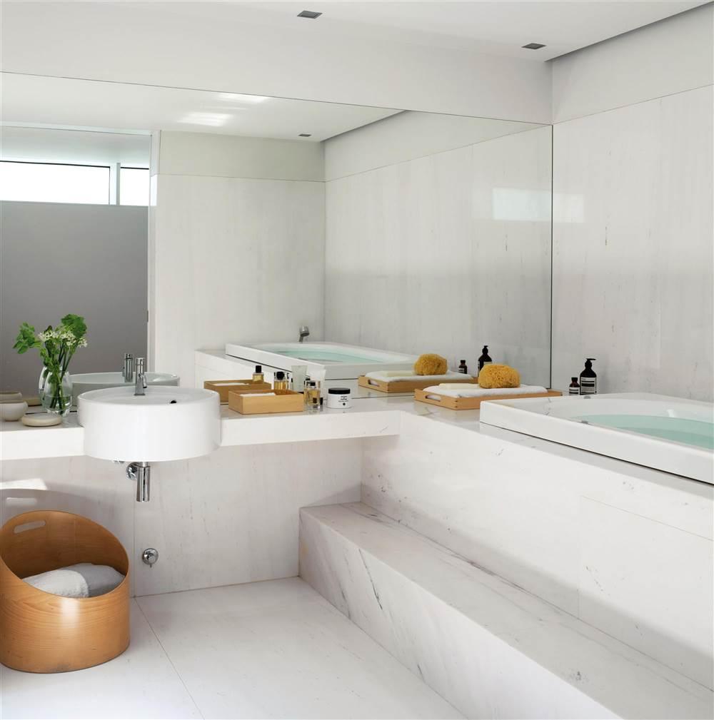 Baño revestido de mármol gris y blanco, con cesta de diseño en madera y gran espejo de lado a lado_240806