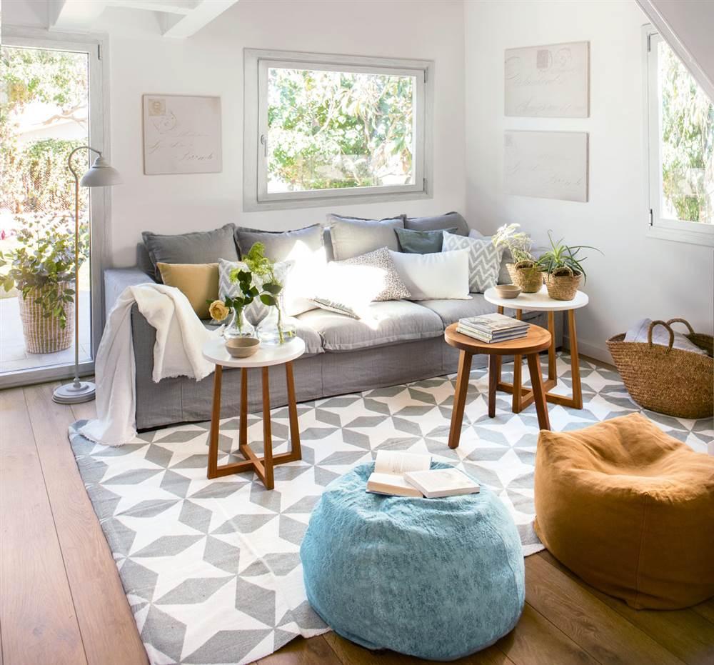Salón con alfombra geométrica en blanco y gris, pufs en mostaza y azul, mesitas auxiliares de madera redondas, sofá gris y lámpara de pie 426033
