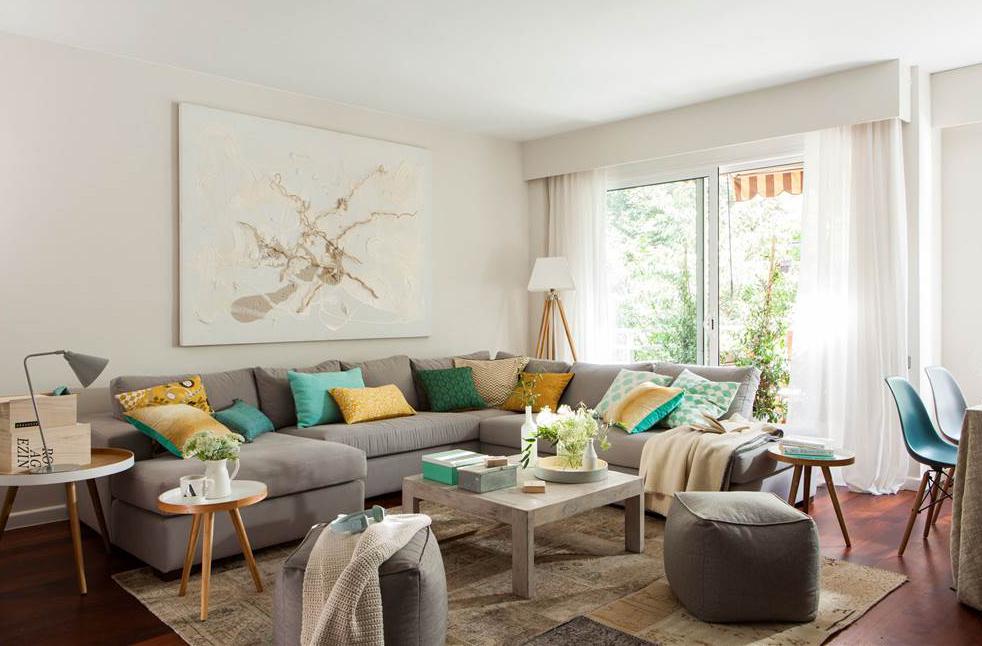 desastres-salon-sofa 1000x666 3d579b78. Sofá gris en L con cojines verdes y amarillos, y gran cuadro