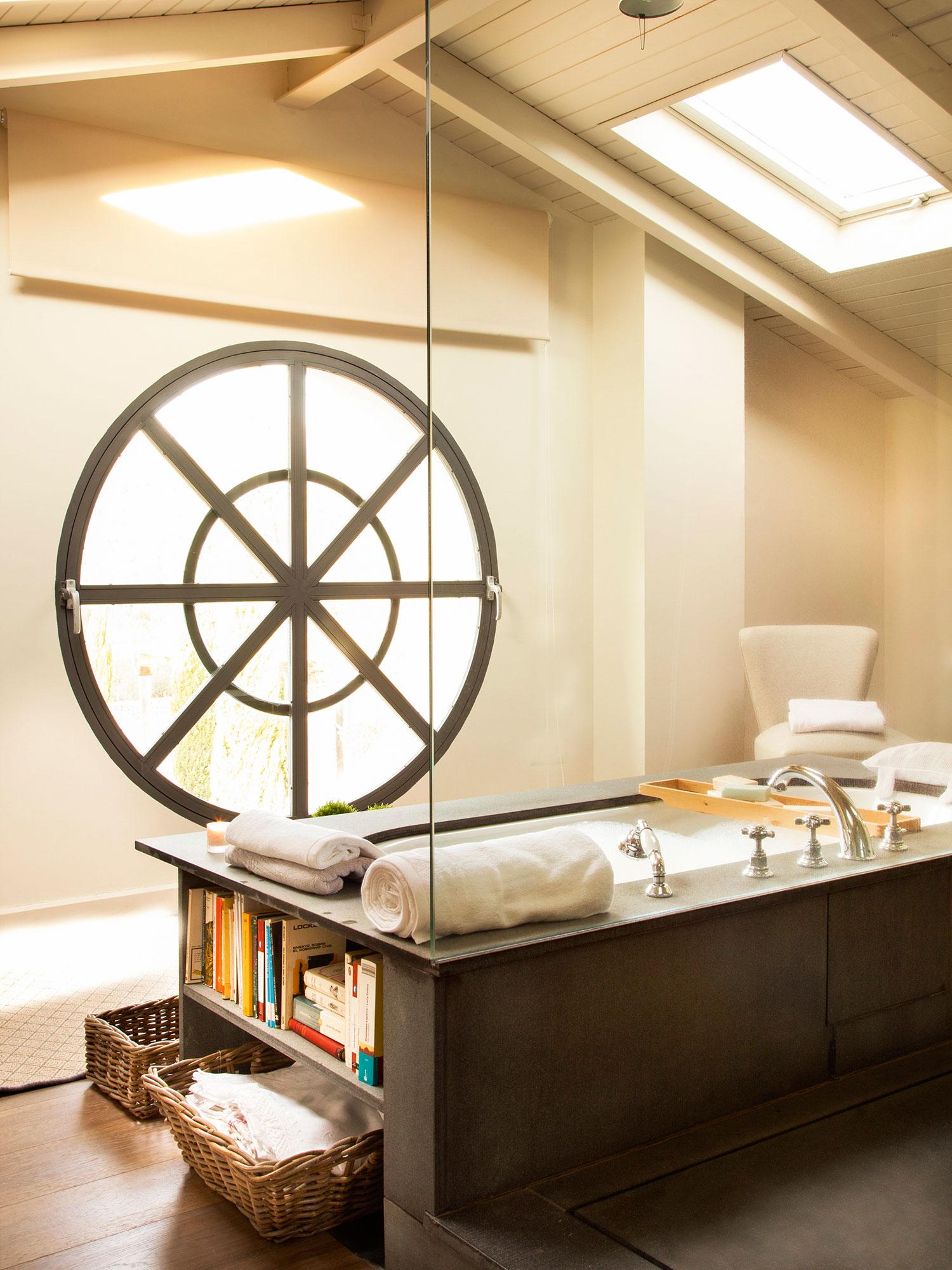 Baño abuhardillado con ventana redonda y bañera con estantes en un lateral.  Un baño de 4a5008639fa4