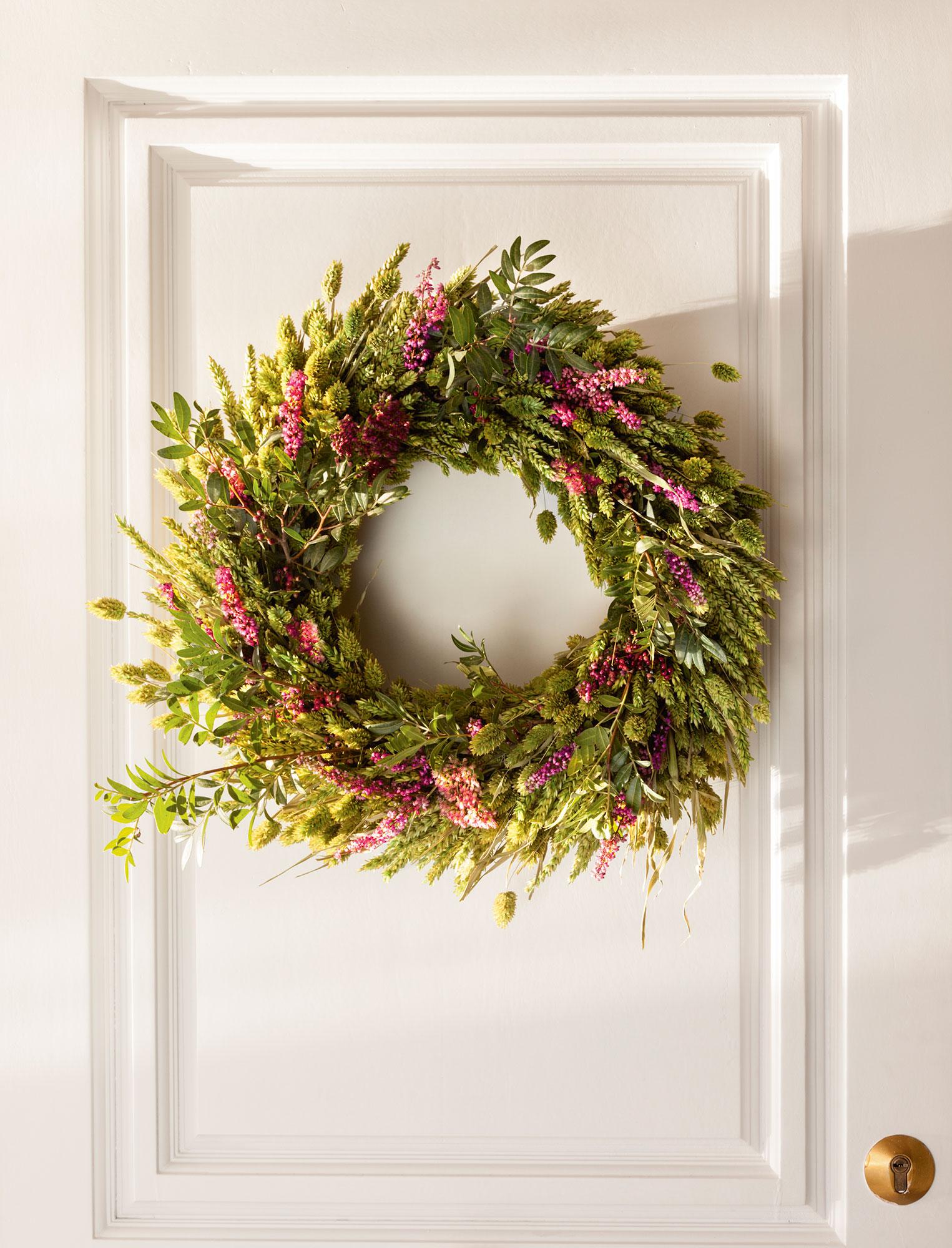 Detalle de corona de Navidad hecha con trigo, plumas y bayas