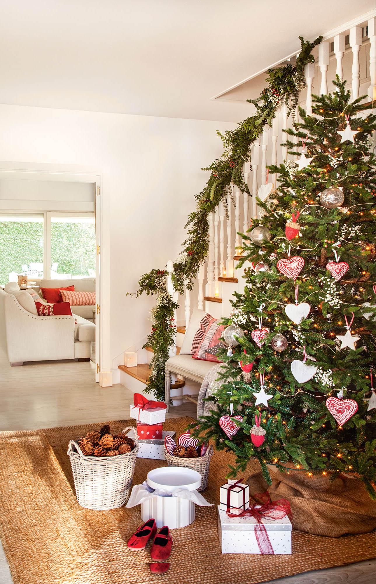 Recibidor con vistas al salón decorado de Navidad con un gran árbol con adornos en rojo y blanco