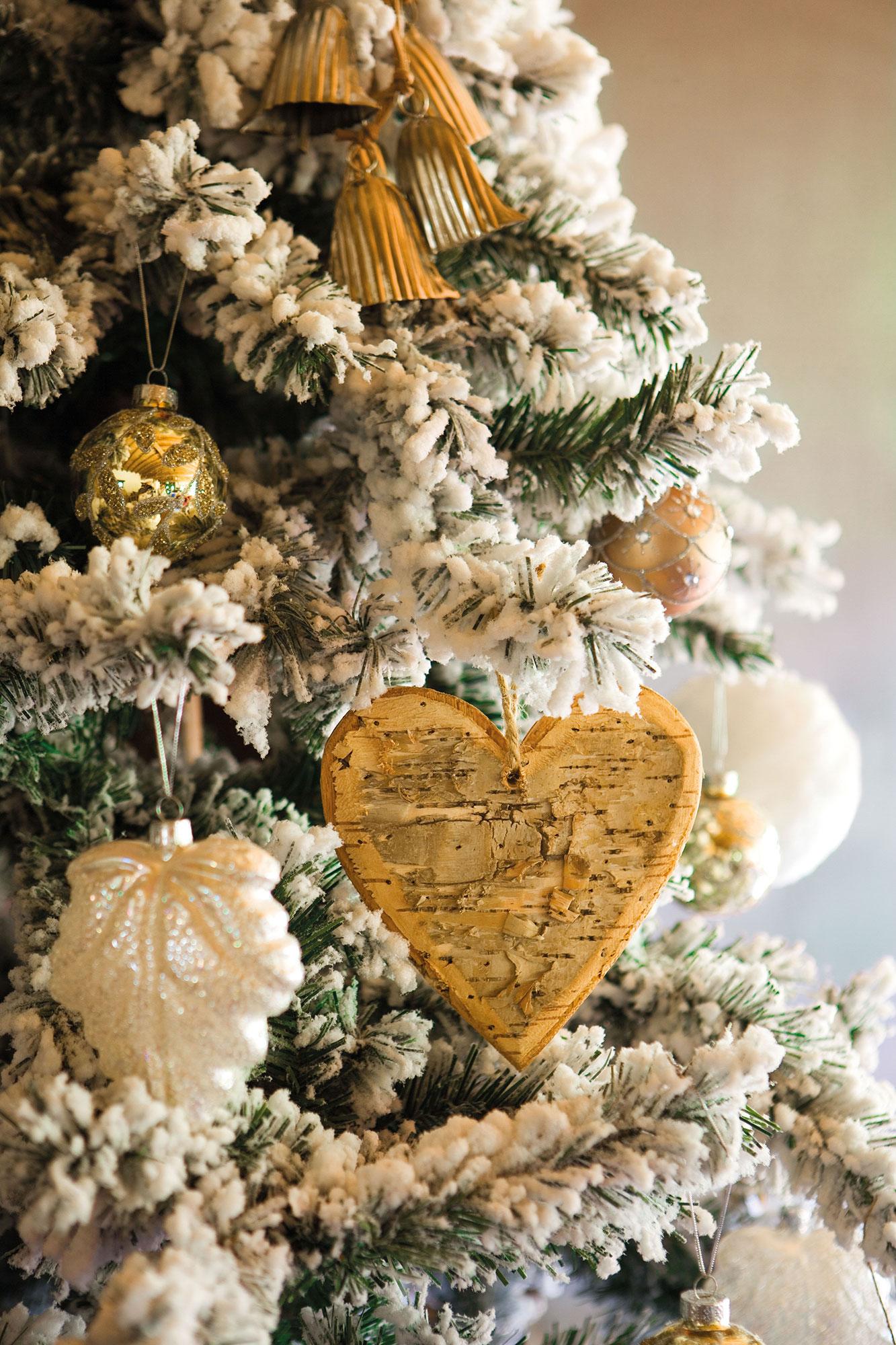 detalle de adornos navideos en blanco y dorado en rbol nevado