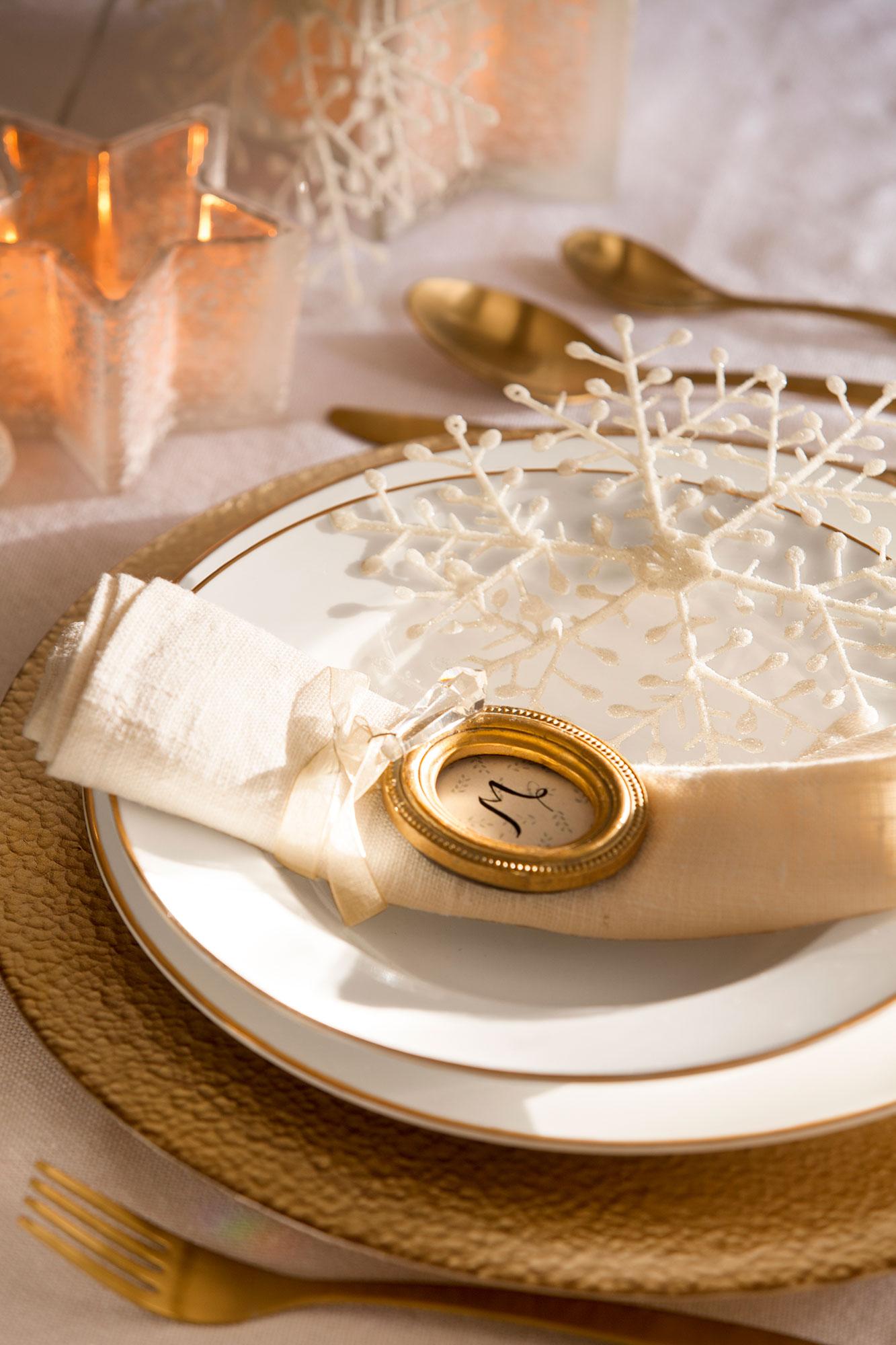 Detalle de broche dorado con la inicial del comensal a modo de servilletero. Mesa decorada de Navidad