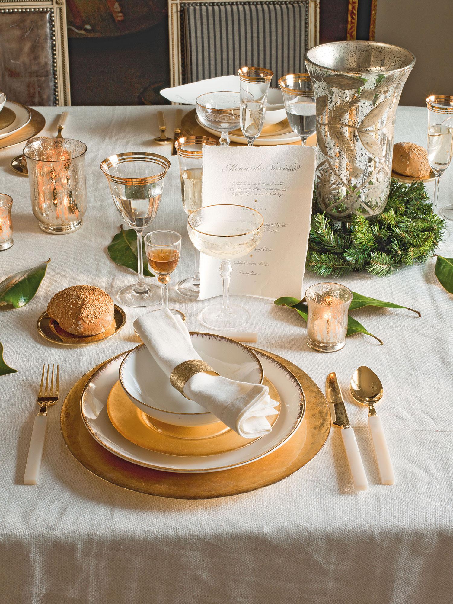Detalle de mesa de comedor vestida en blanco y dorado para comida de Navidad