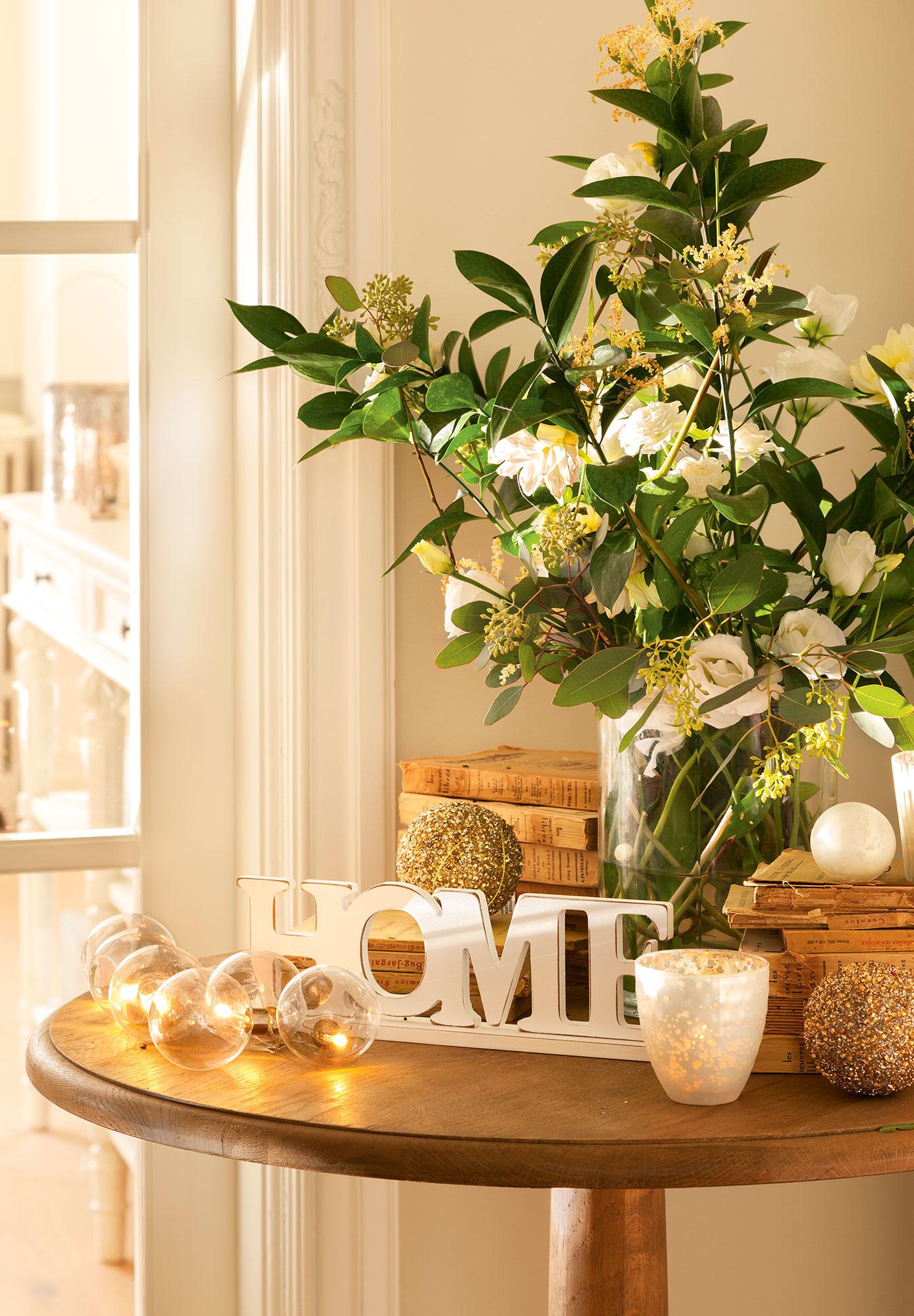 Detalle de rincón del salón con composición floral y detalles navideños en blanco y dorado