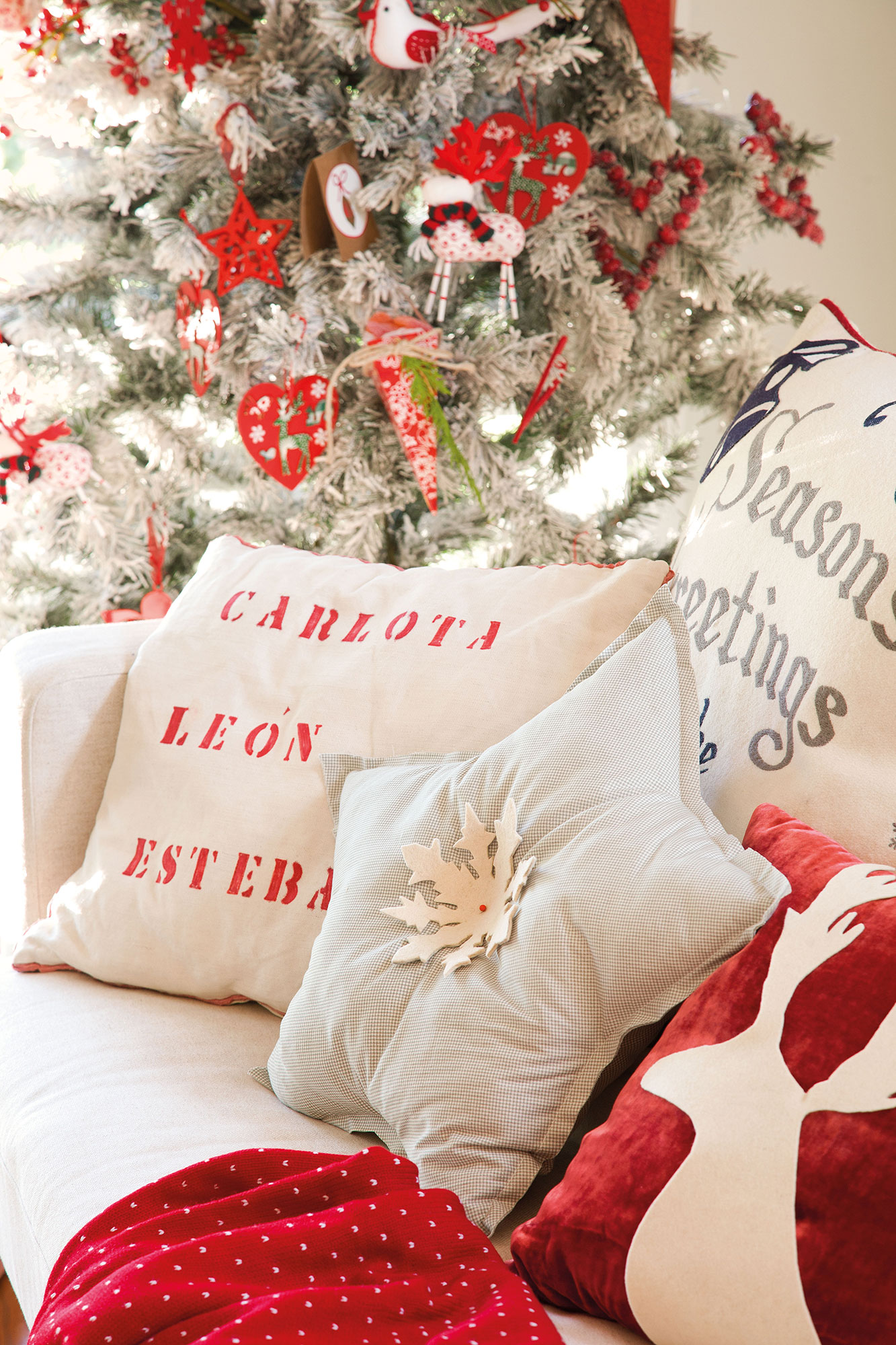 Detail of cushions decorated with Christmas motifs with tree in the background. Custom Christmas pillows
