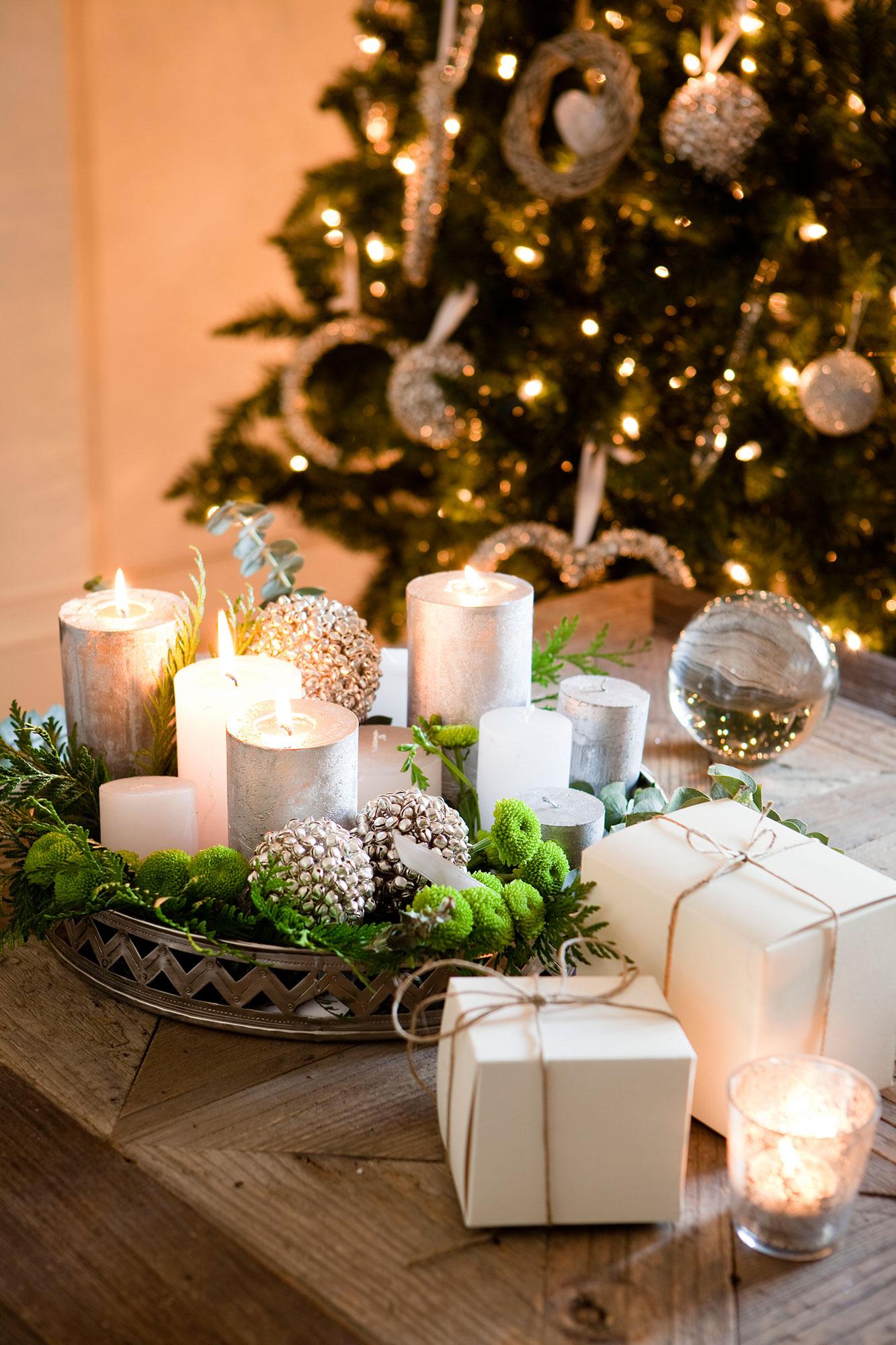 detalle de centro de mesa de navidad hecho con bolas con cascabeles y velas