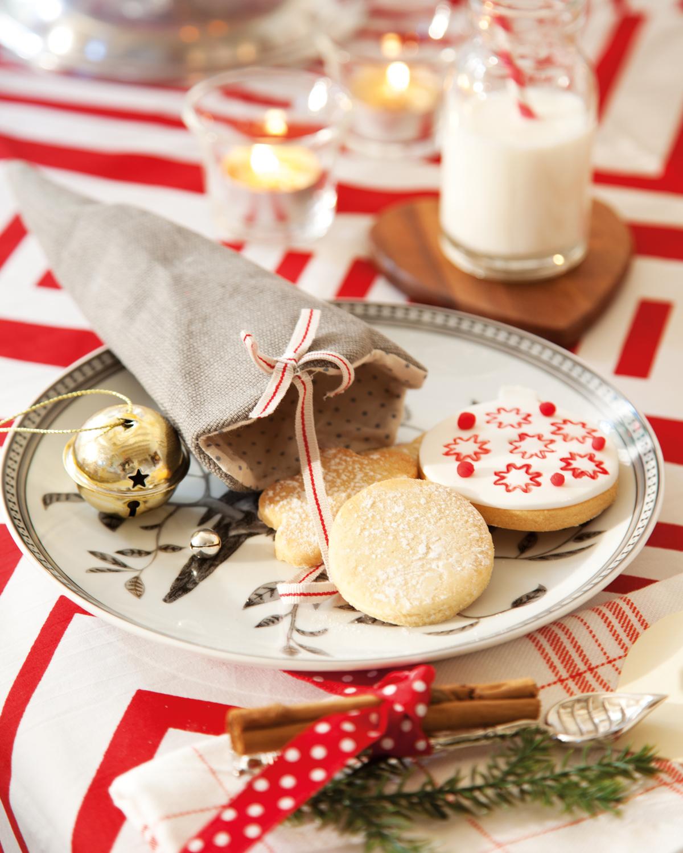 00374294. Plato con cucurucho de tela y galletas navideñas sobre mantel blanco y rojo (374294)