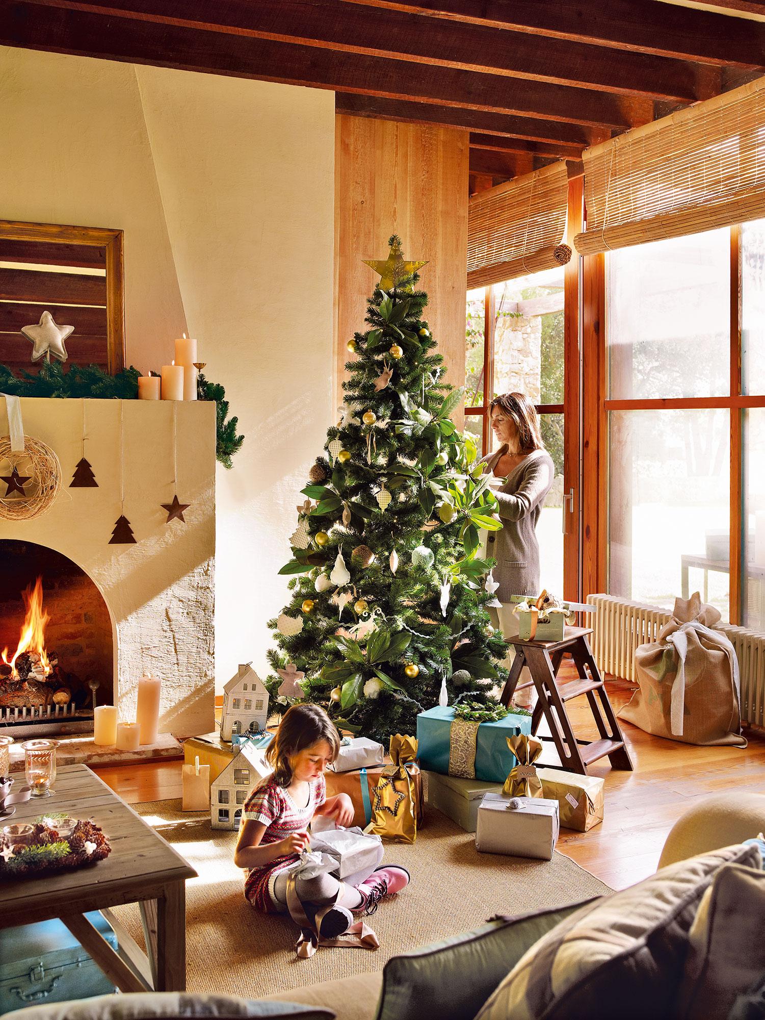 Salón decorado con árbol de Navidad con niña y mujer
