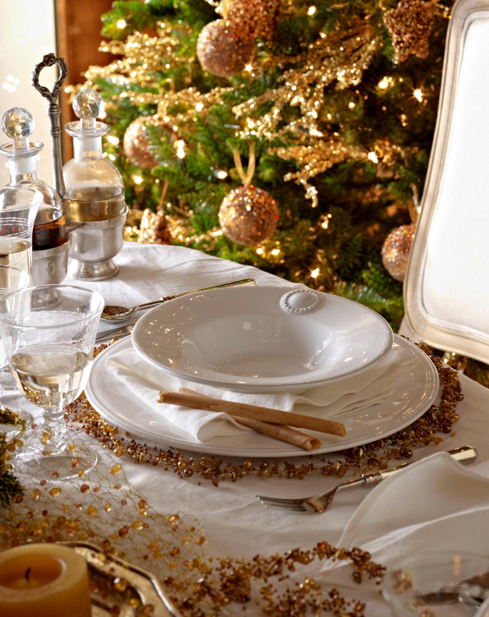 o mesa de navidad con vajilla blanca y decorada con detalles dorados o