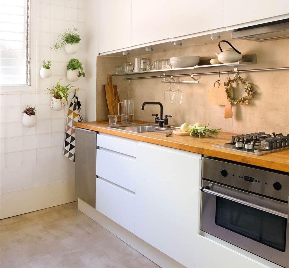 cocina con muebles en blanco encimera de madera y suelo de