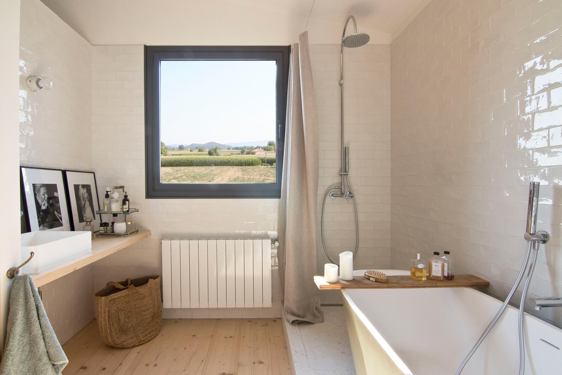 Baño Blanco Suelo Madera:Salón con sofás oscuros, cuadros de colores, butacas y mesitas