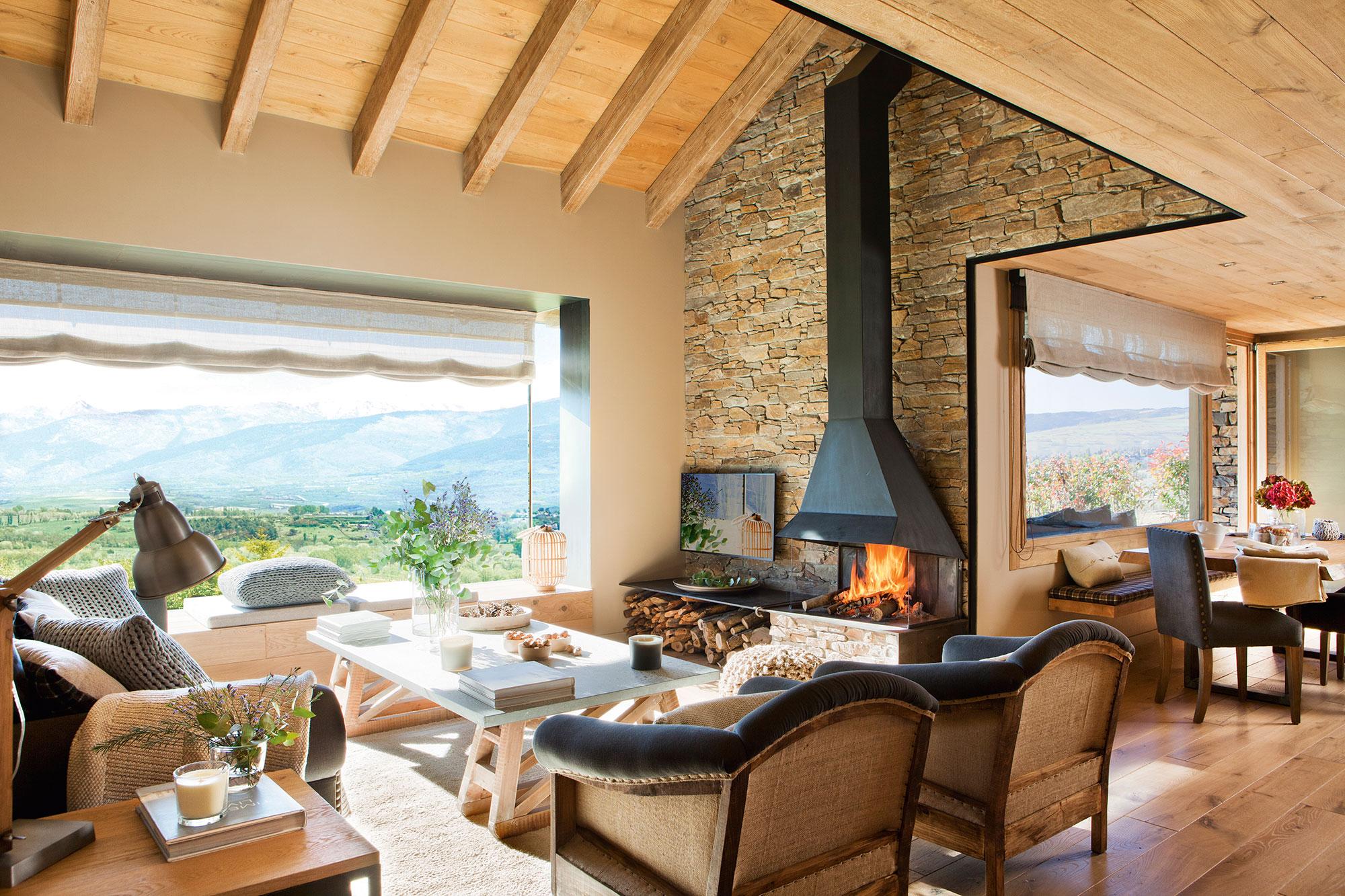 saln rstico con vigas de madera pared de piedra chimenea y vistas al comedor