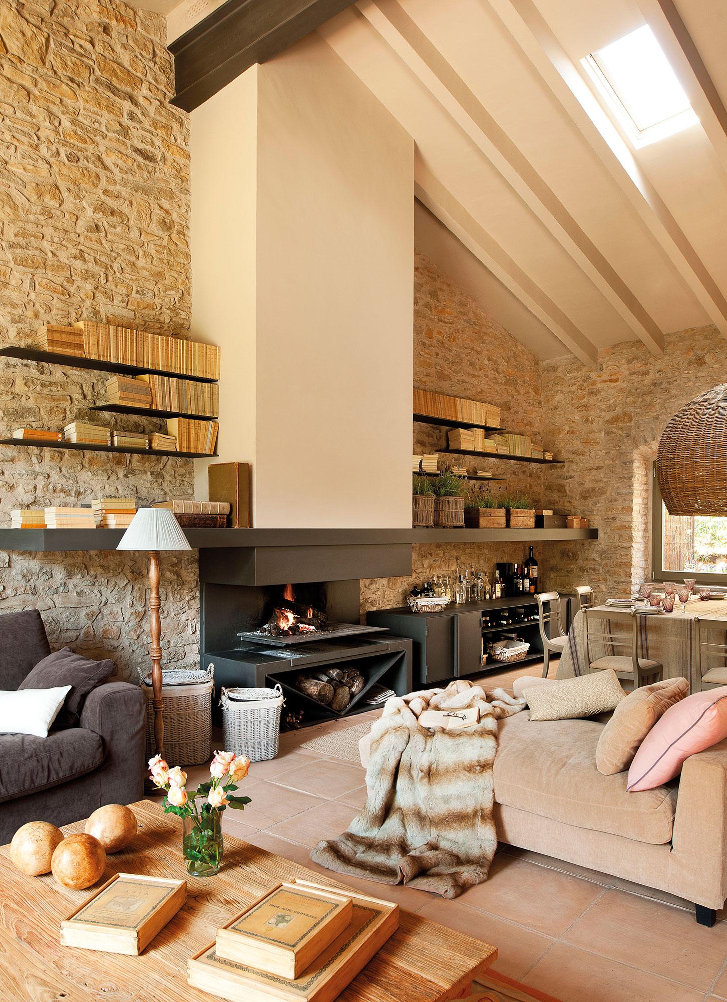 saln rstico con chimenea pared de piedra y ventana cenital