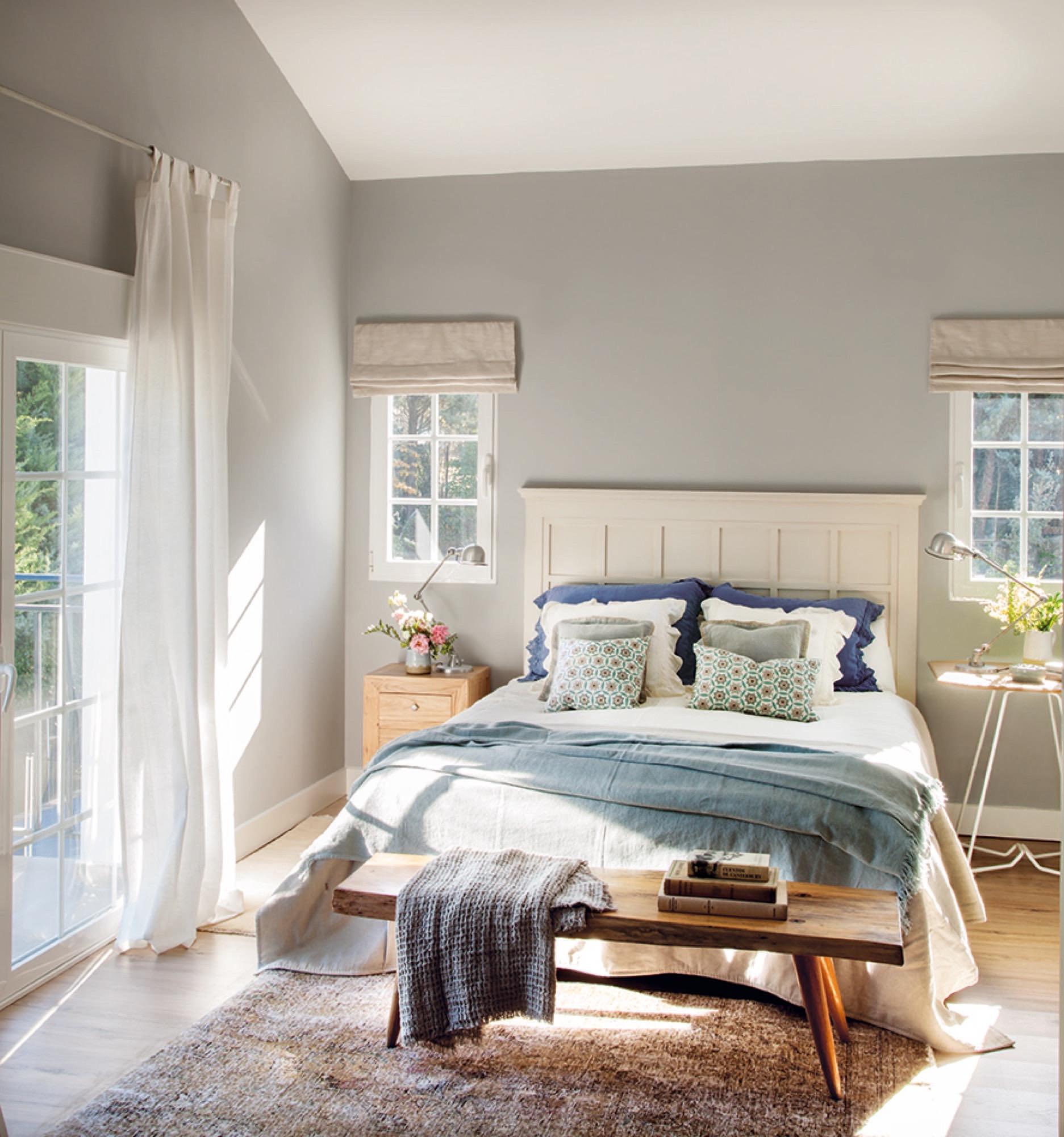 dormitorio con cabecero blanco y tonos azules