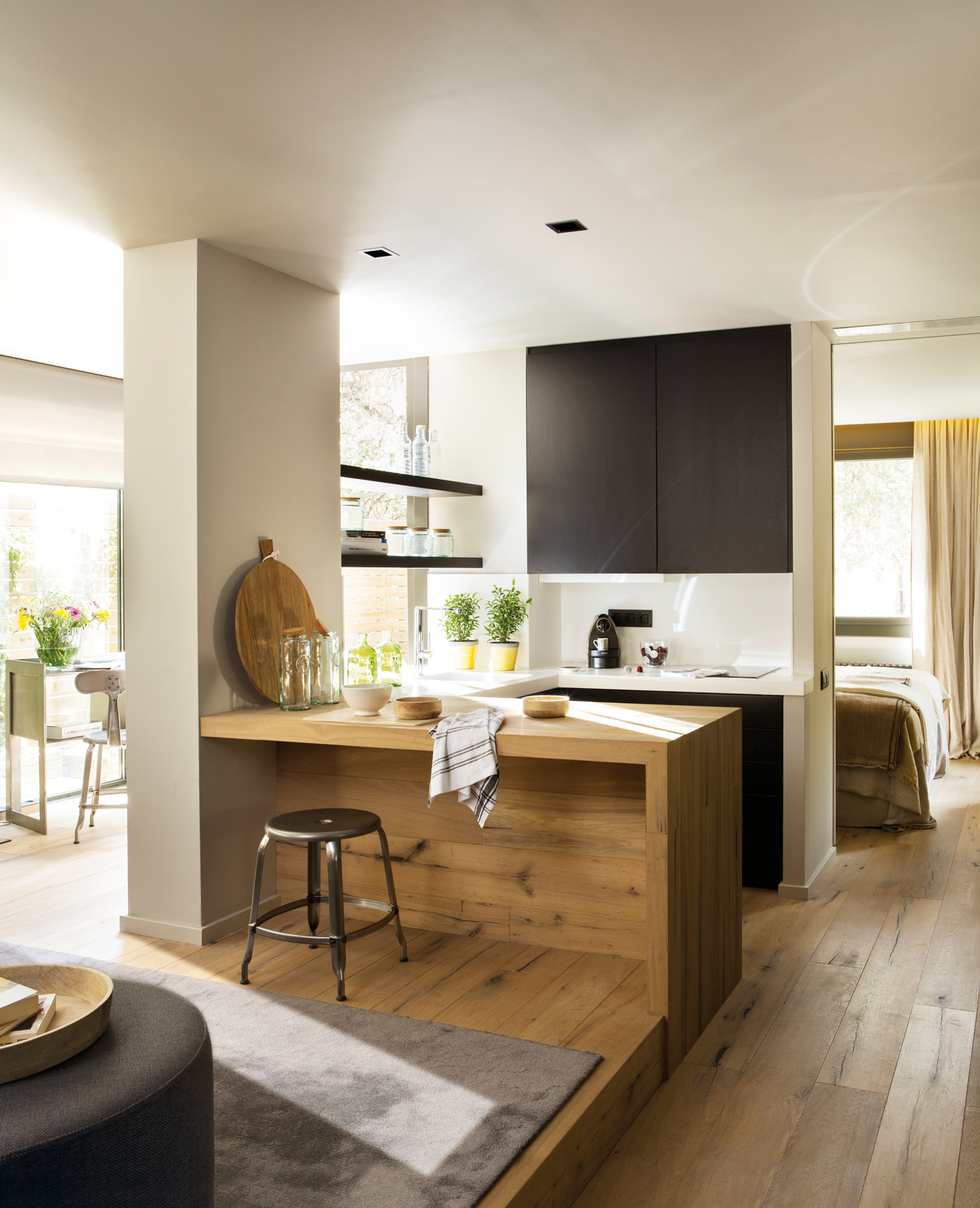 cocina con mesa integrada en saln madera y negro taburete