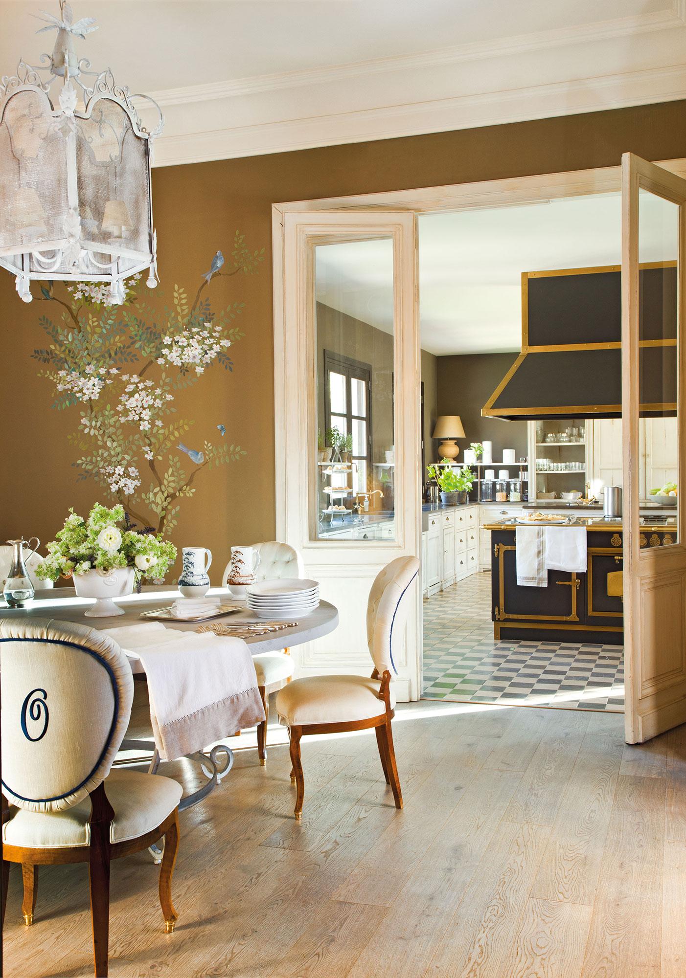 Comedor con vistas a la cocina con mural de árbol y pajaritos en la pared. El jardín, en el comedor