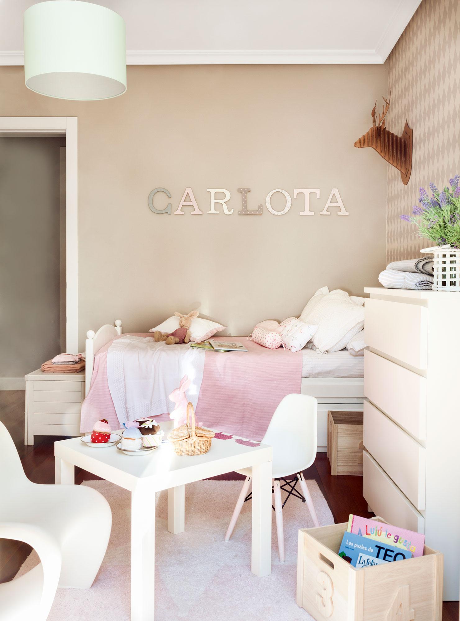 Dormitorio infantil con papel pintado y letras en la pared con el nombre de Carlota. El reino de Carlota