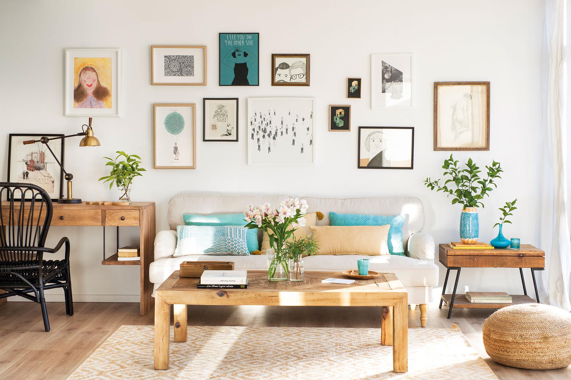 Salón con pared del sofá con composición de cuadros y láminas. Una pared... a cuadros