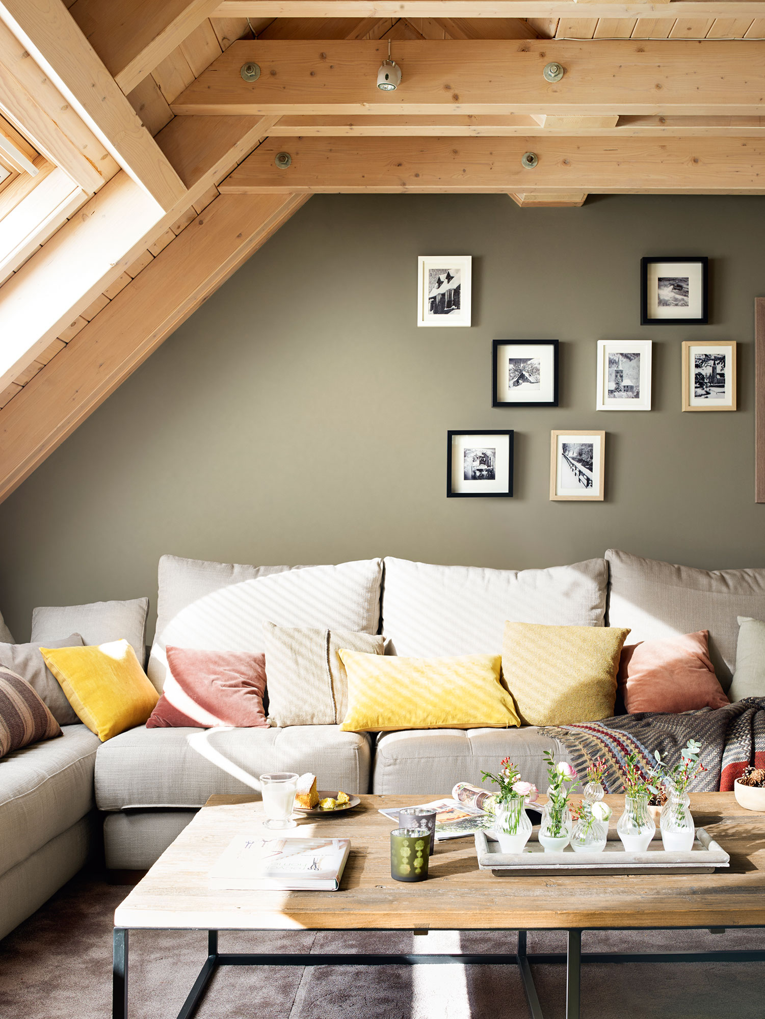 Semitoma de salón con techo de madera y composición de cuadros en blanco y negro sobre pared verde grisácea. Composición de fotos en blanco y negro