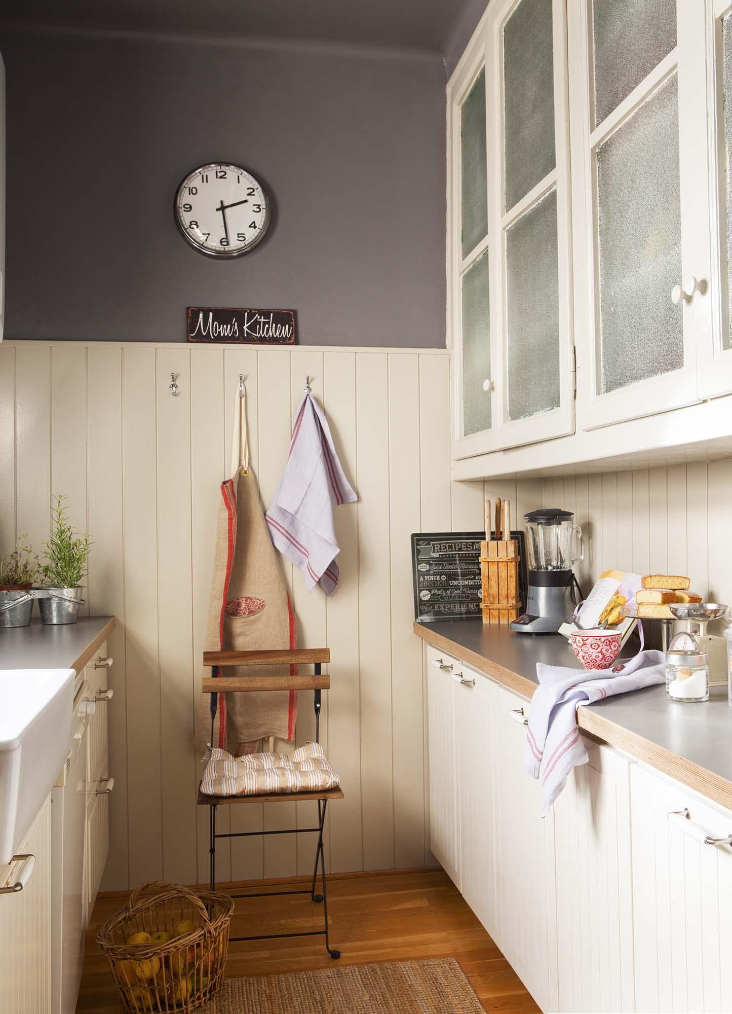 Cocina con mobiliario en blanco, pared gris y arrimadero de lamas verticales en blanco. Un arrimadero que viste y protege