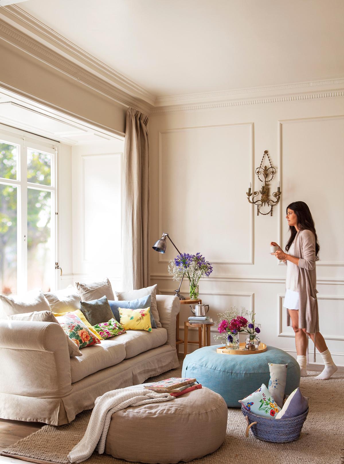 Salón con sofá y pufs, y chica bebiendo té (00368606)
