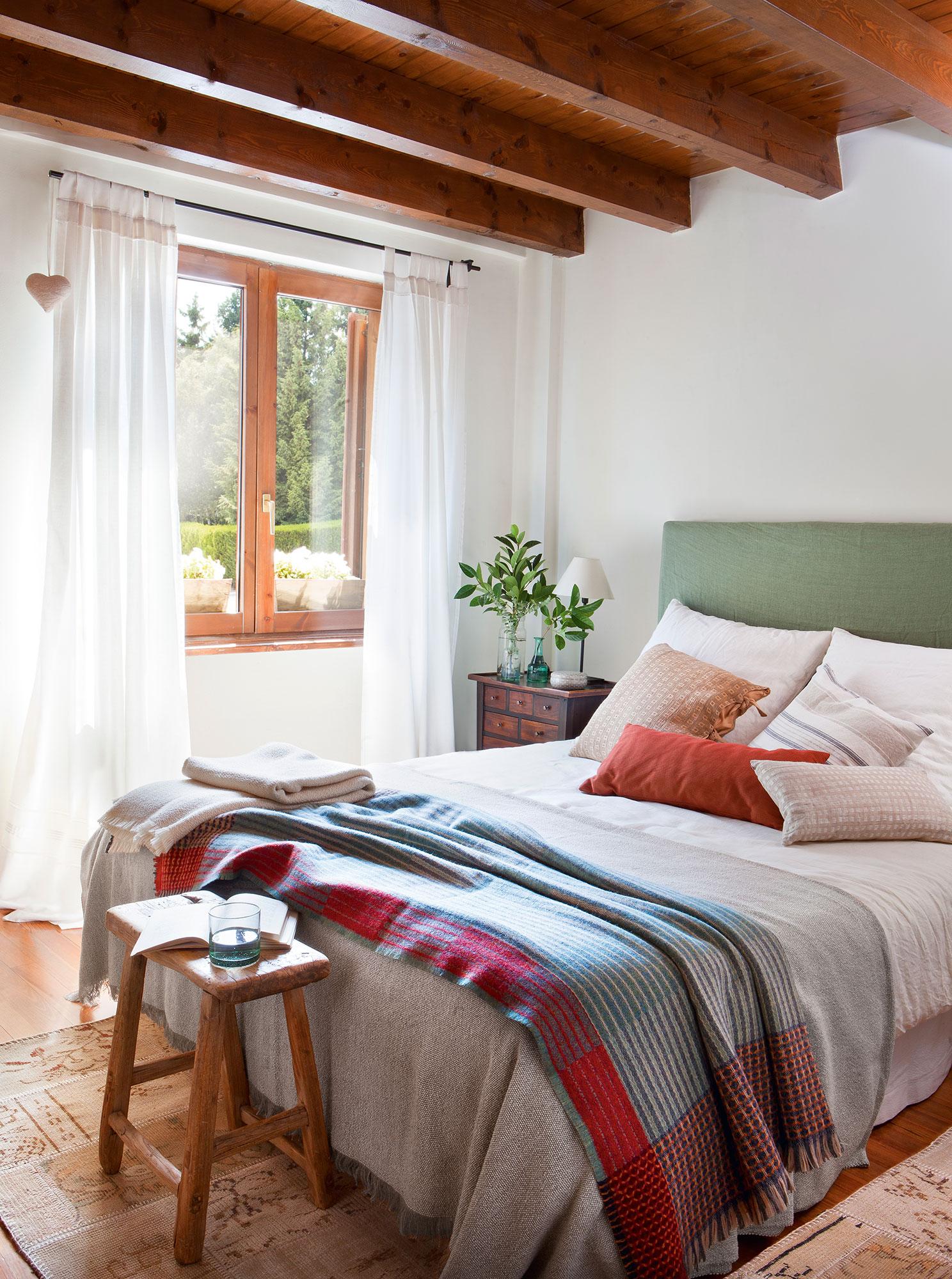 dormitorio rstico con paredes en blanco y cabecero tapizado en verde