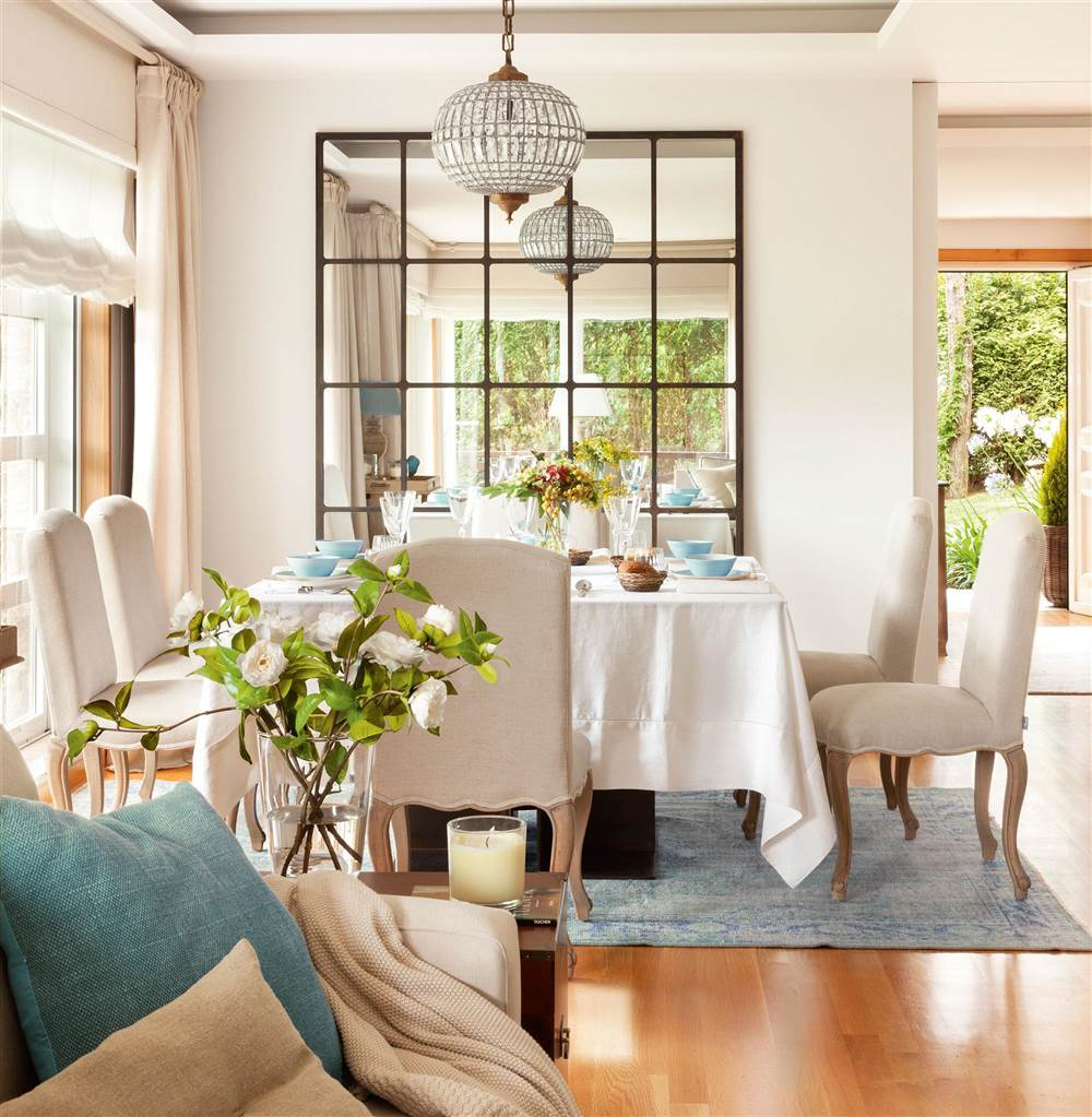 Dining room with square table, upholstered chairs, mirror and glass lamp