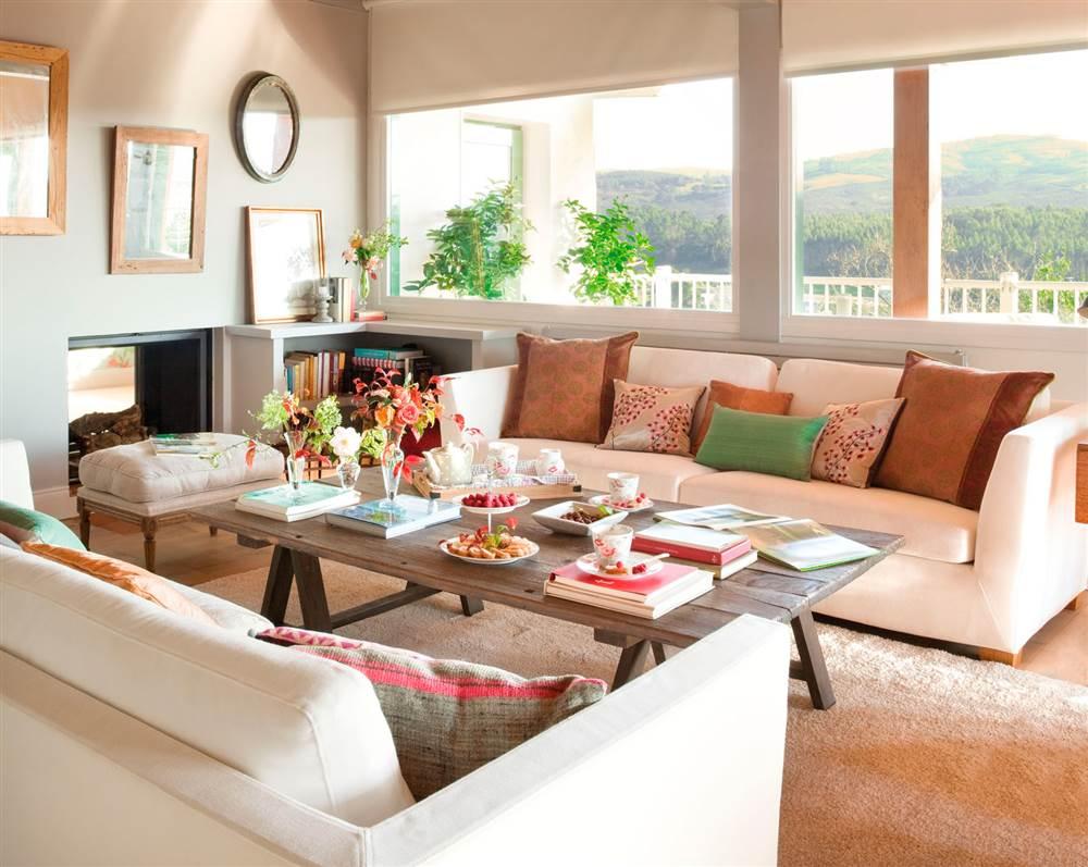 Sofás blancos con cojines en marrón y verde y mesa de centro de madera