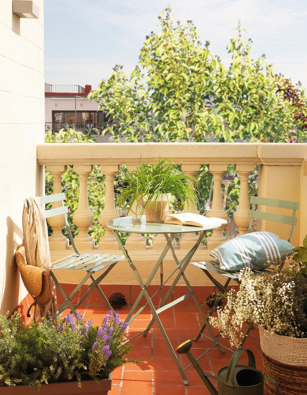 417f7736263 Terraza con plantas y pequeña mesa redonda de exterior-00442270. Sillas y