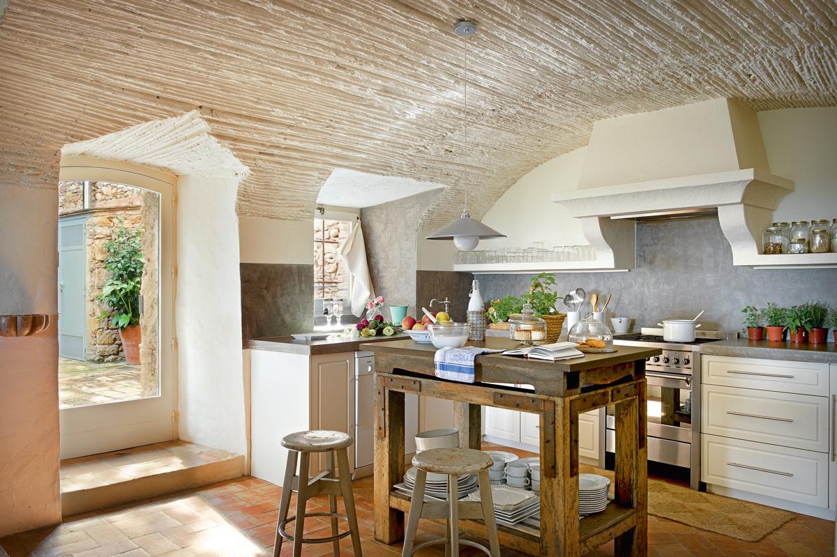 cocina rstica con techo abovedado pavimento de toba encimera de y mesa tocinera
