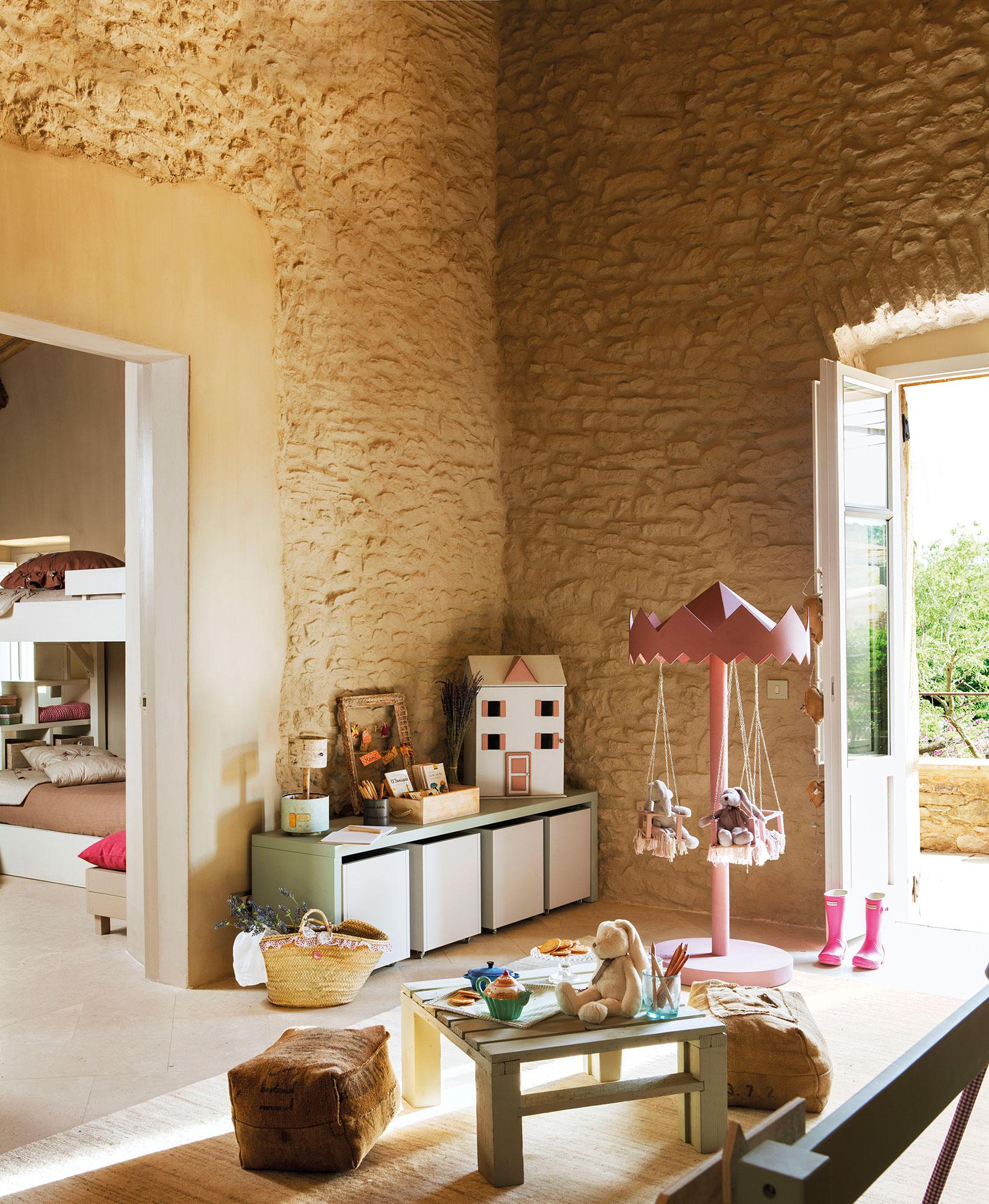 dormitorio infantil en casa rstica con paredes de piedra con mueble bajo con books para juguetes