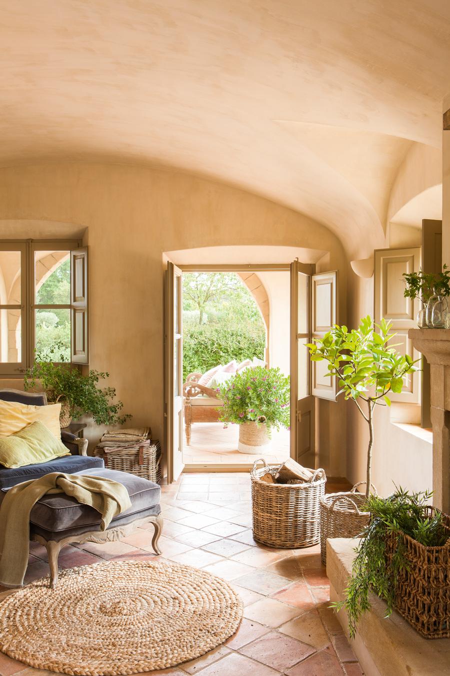 Casa rústica con techo abovedado, salida a porche. Suelo de toba, plantas, cestos y butaca azul y alfombra de fibra 00433885